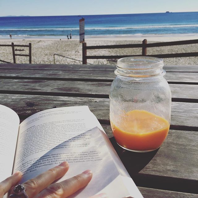 Sneaking in some quiet time before the rush of work begins! ______________________________________________#byronbay #beach#relax#reading #juice #selfcare #lifestylestolast #wellnesscoach #tuesday #winter #sunshine #timeout #taketimeforyourself #whales #health #wellness #ocean #soul #morning #work #breakfast #orange #carrot #ginger