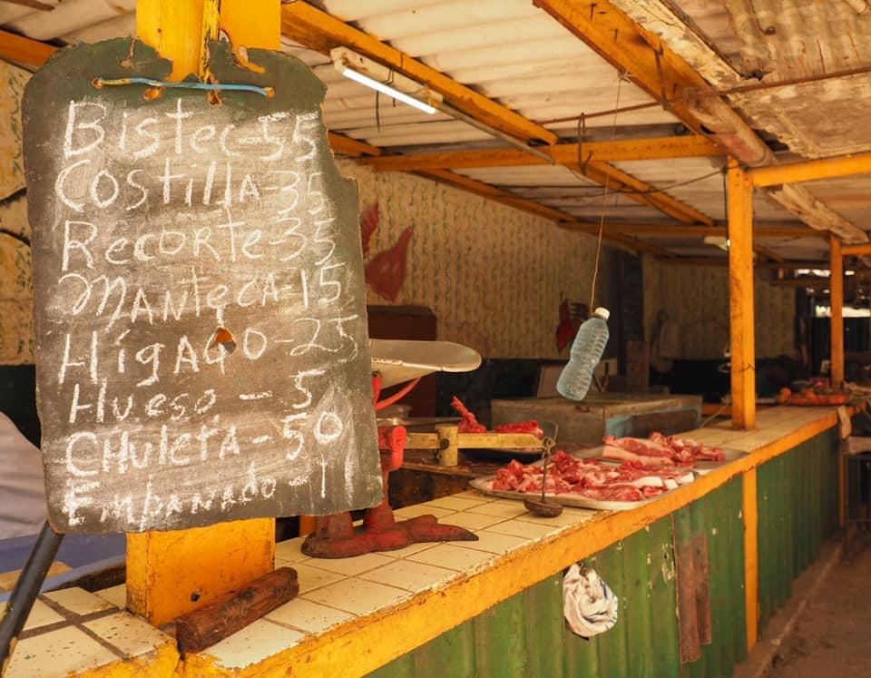 Open-air meat market in Central Havana. The swinging water bottle bats flies away.