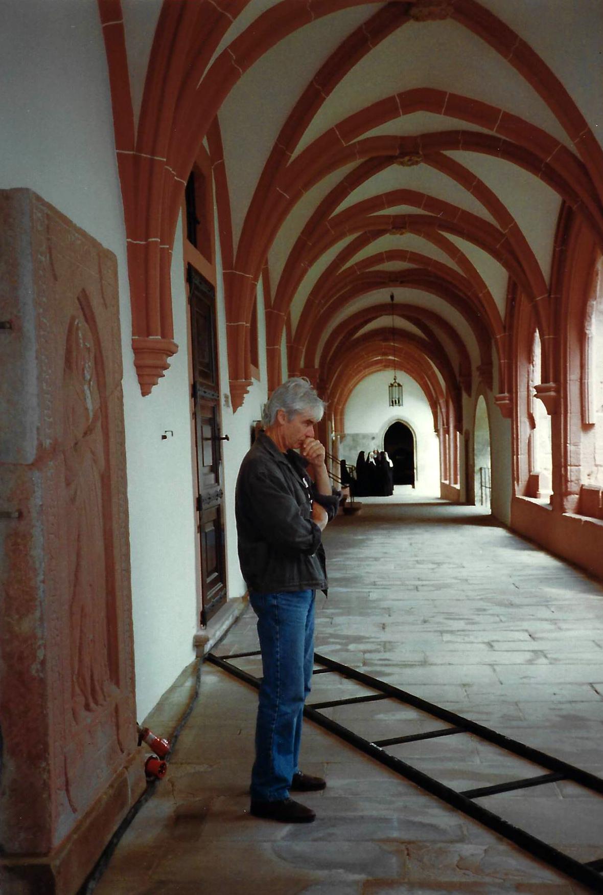 Peinzende regisseur, Wil van Neerven, met op de achtergrond de nonnen van Hildegard (het koor Cercamon)