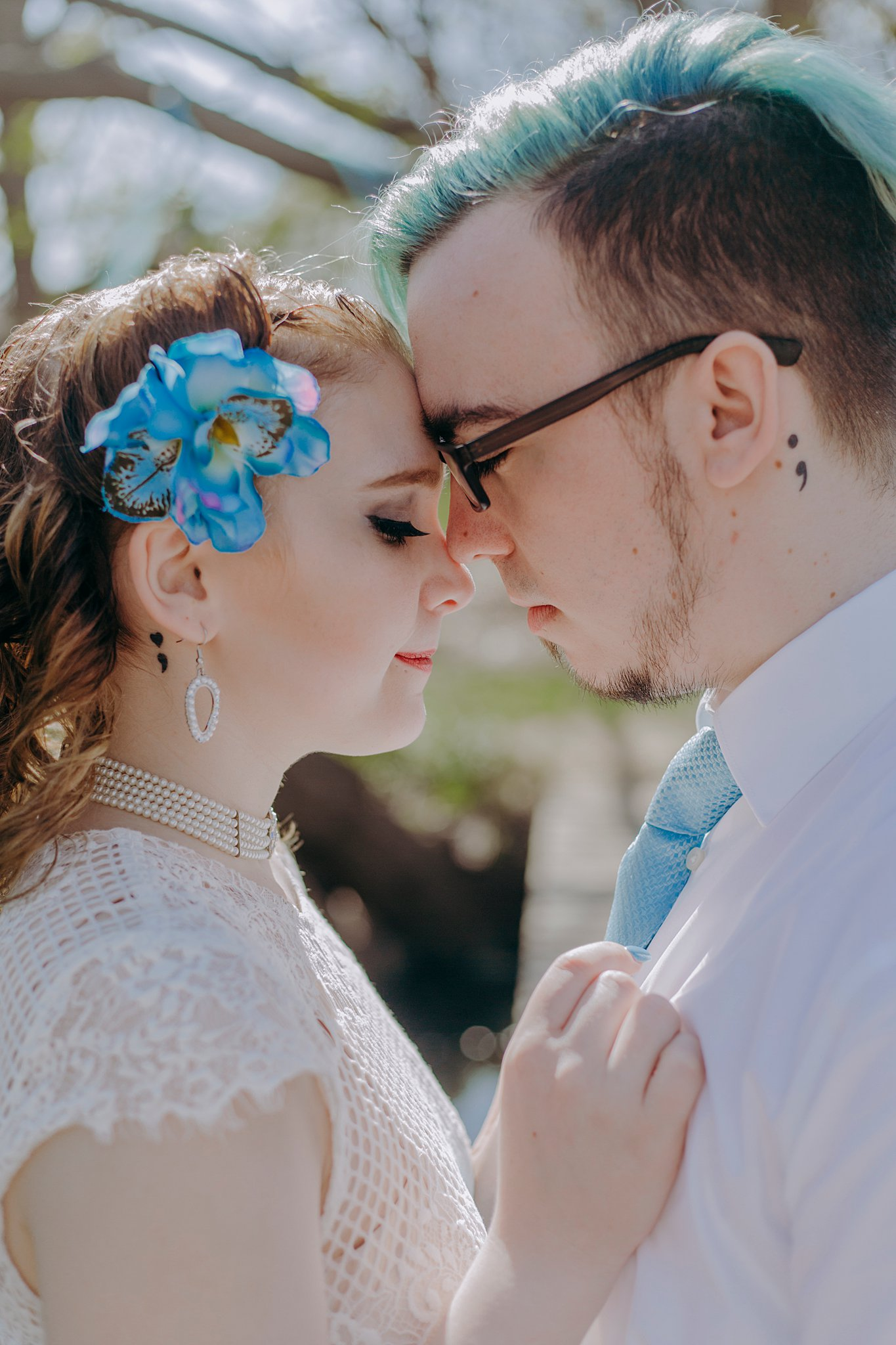 A recently eloped couple puts their foreheads together, closing their eyes and taking in the moment