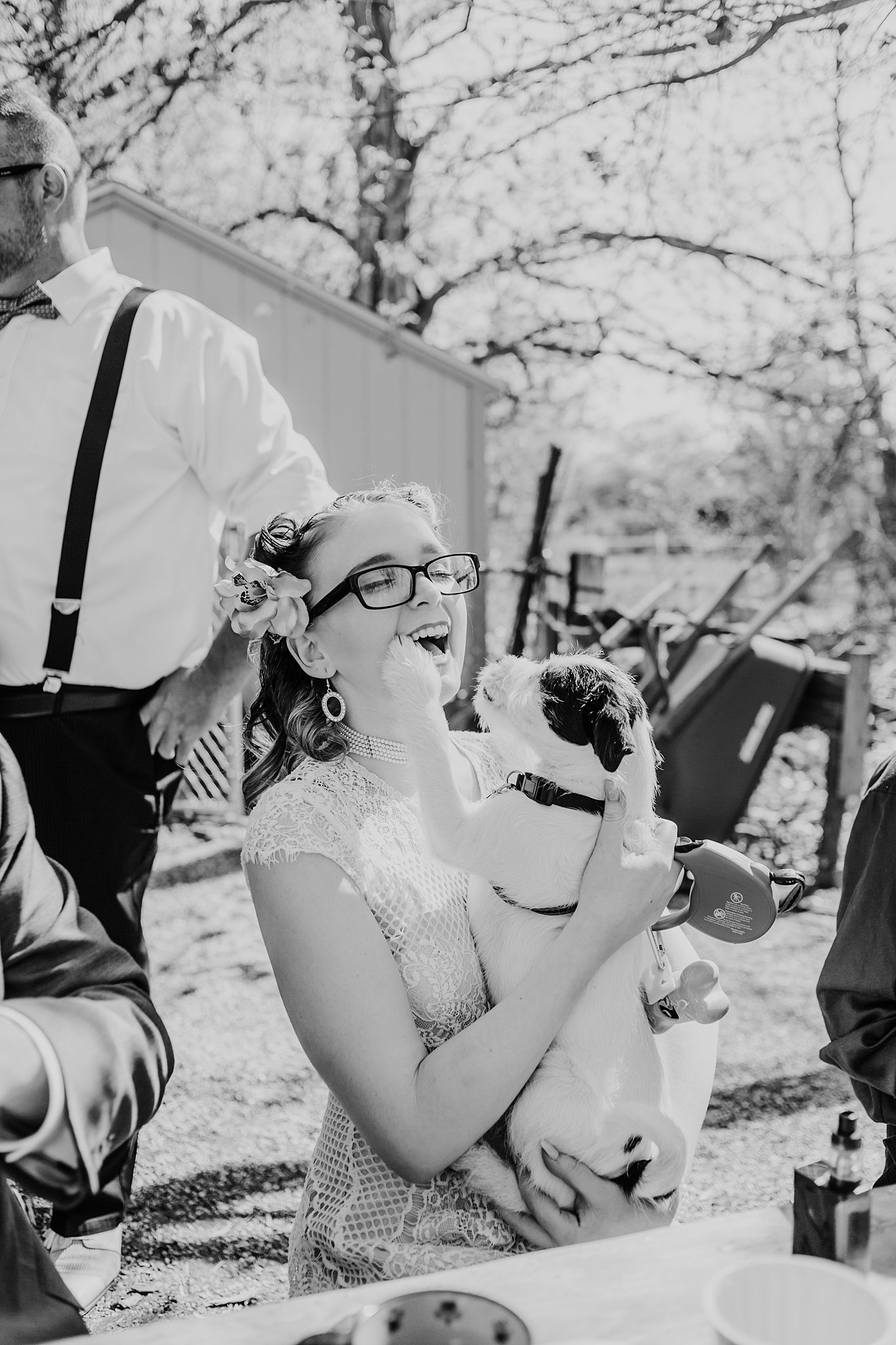 The bride laughs while holding a puppy.