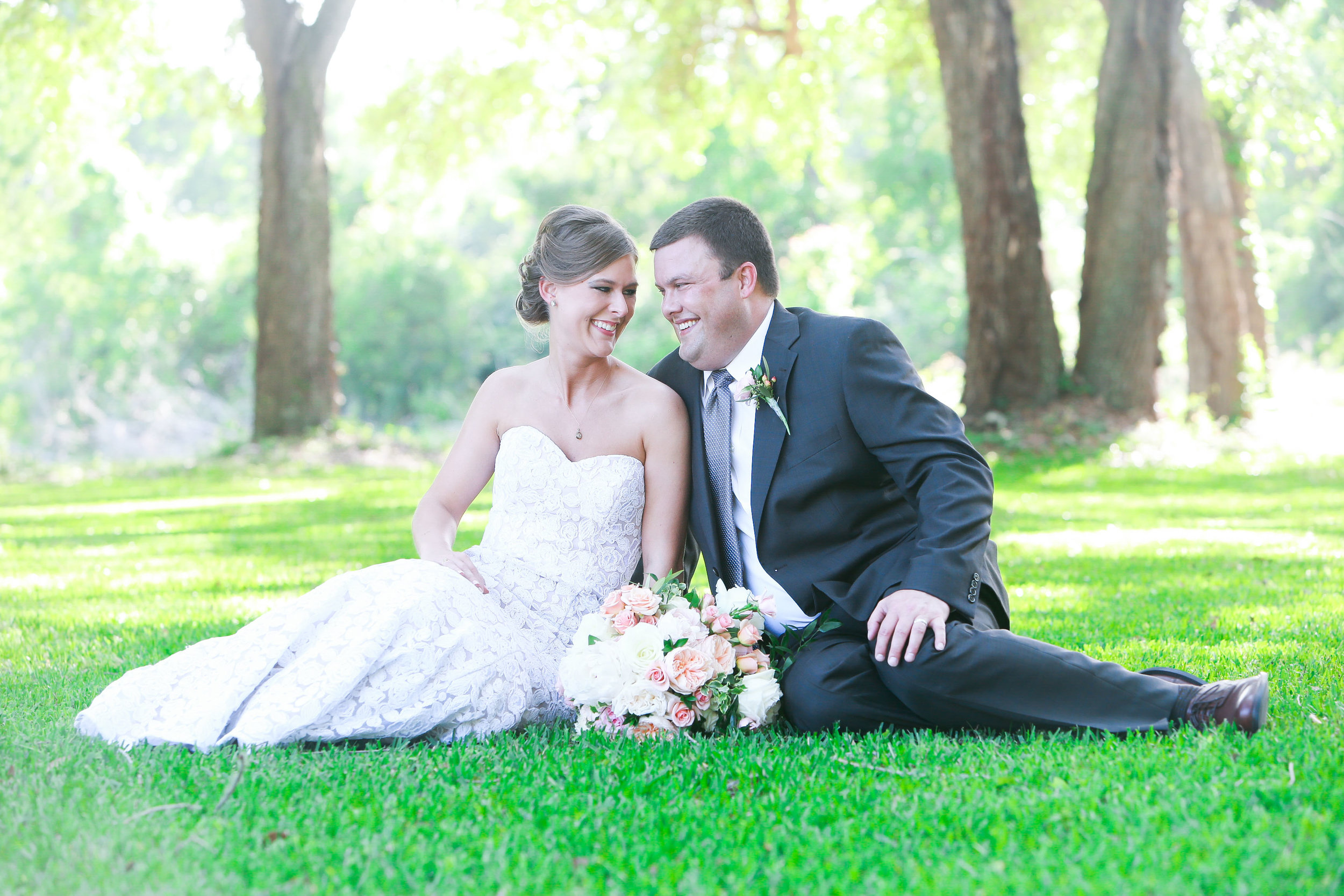 Married couple sit in grass laughing with each other