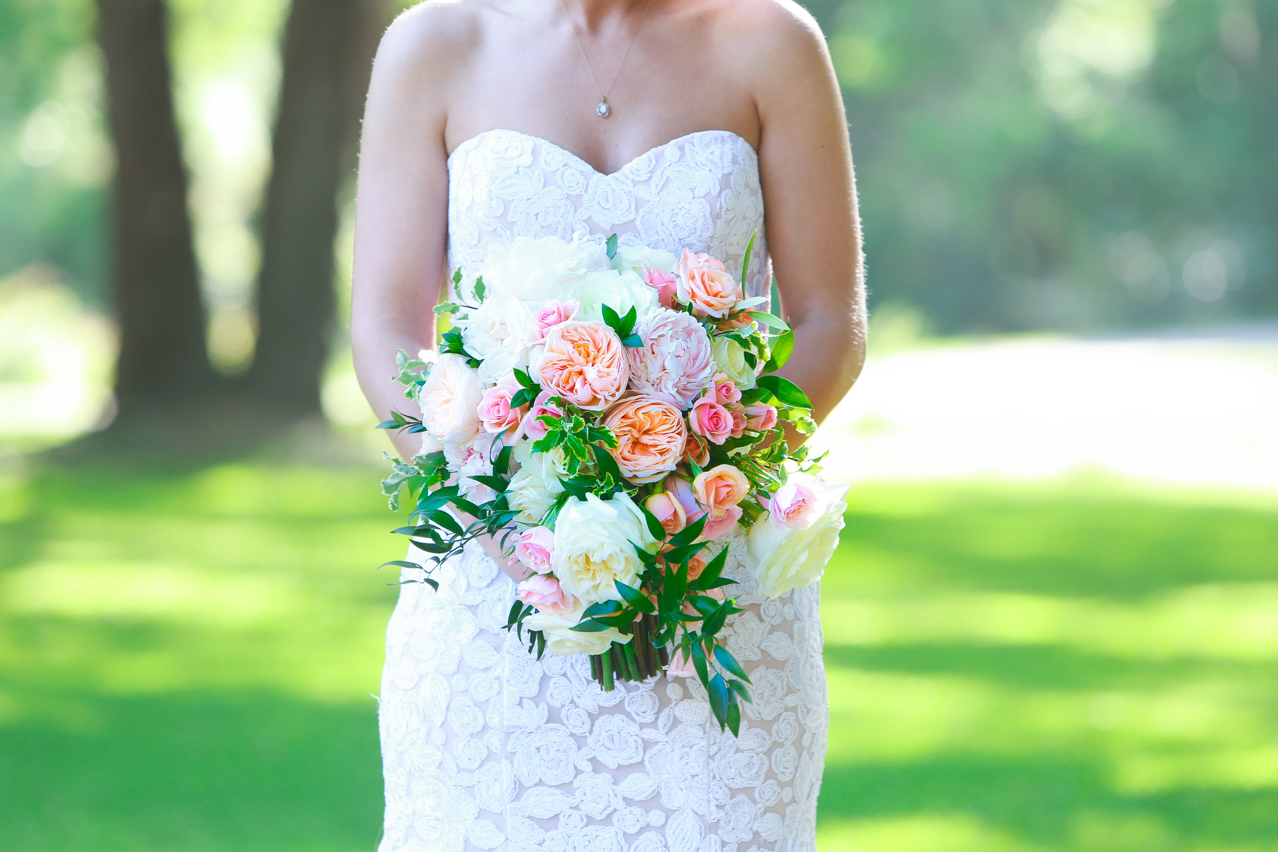 Beautiful pink and white rose bouquet being held by a bride