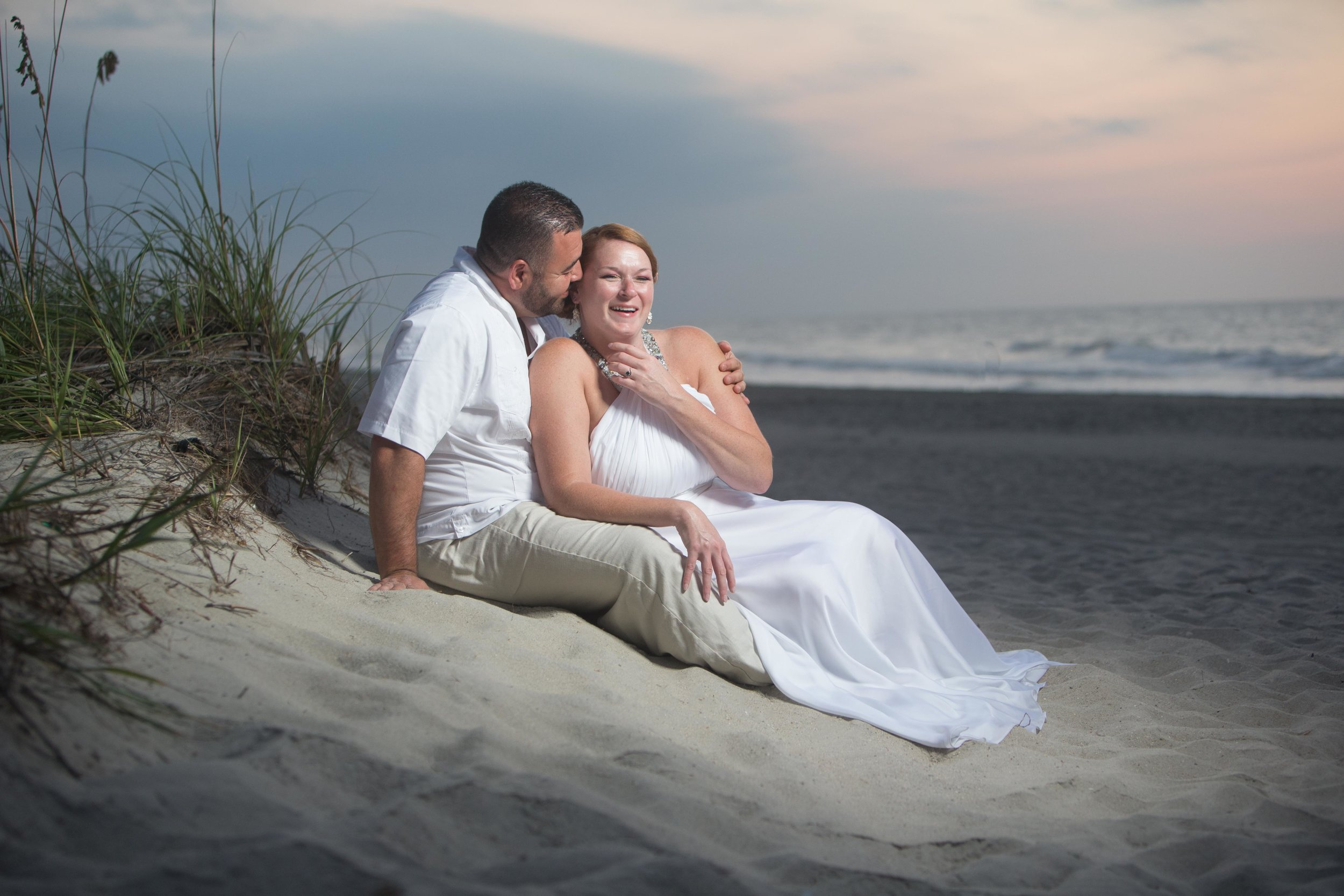 Bride and groom lounge in the sand on the beach enjoying the sunset