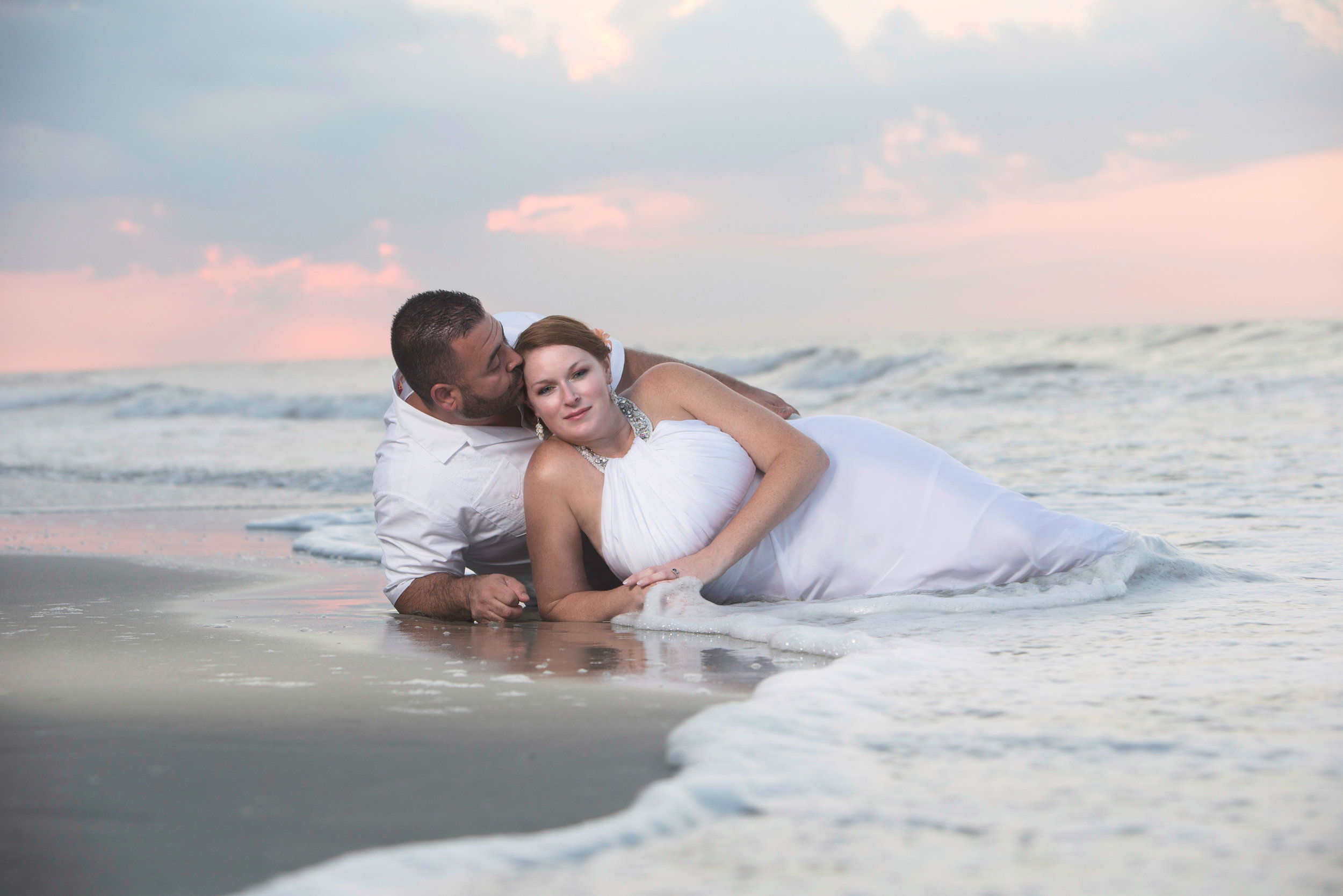 Couple lays on the beach in the tide while the husband kisses his wifes forehead