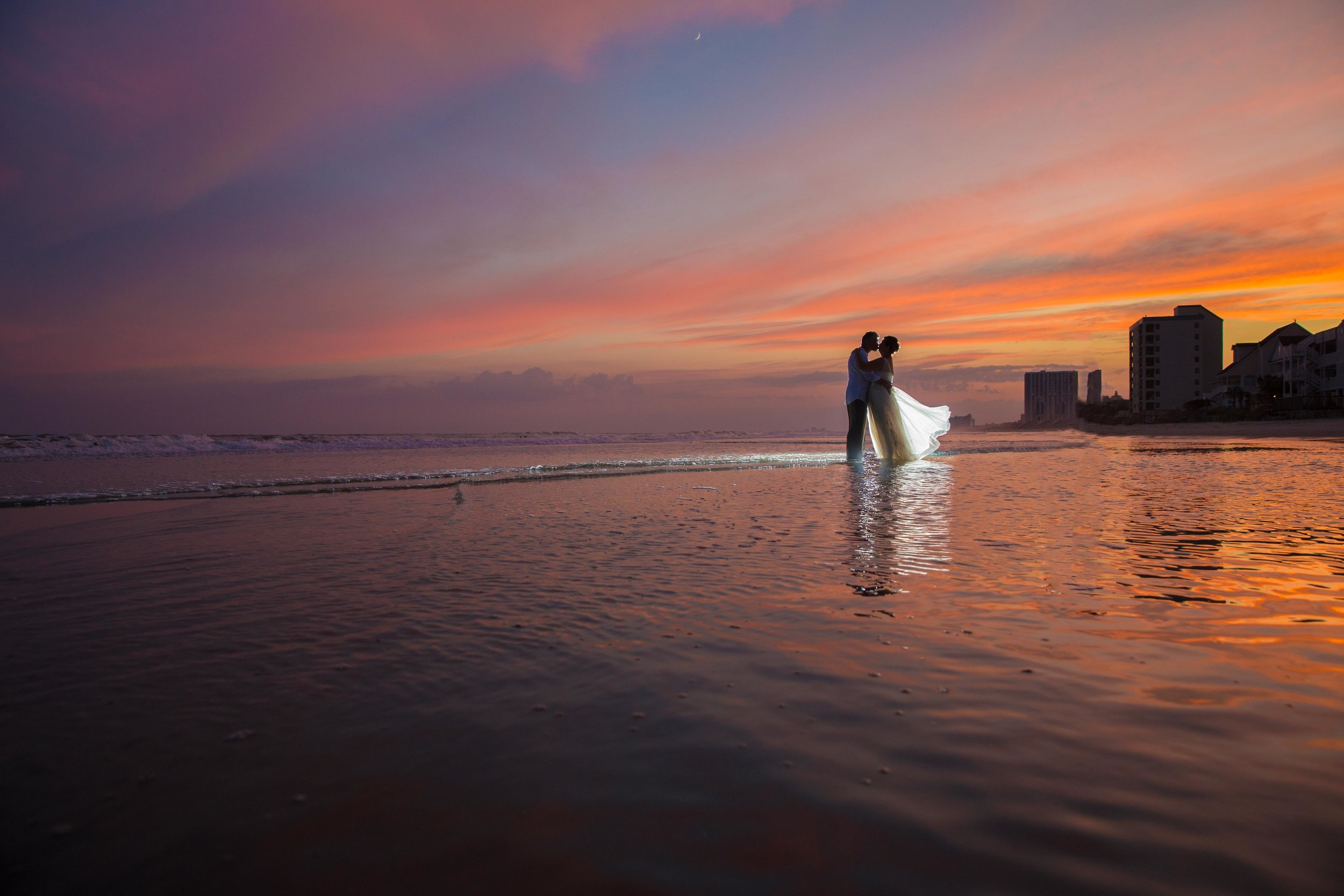 Gorgeous sunset portrait of a newlywed couple on the beach