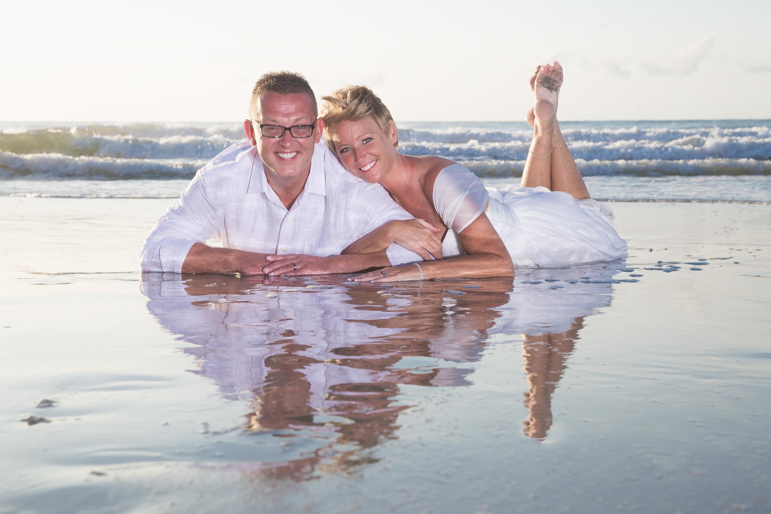 Husband and wife lay in shallow water of the beach smiling together at the camera