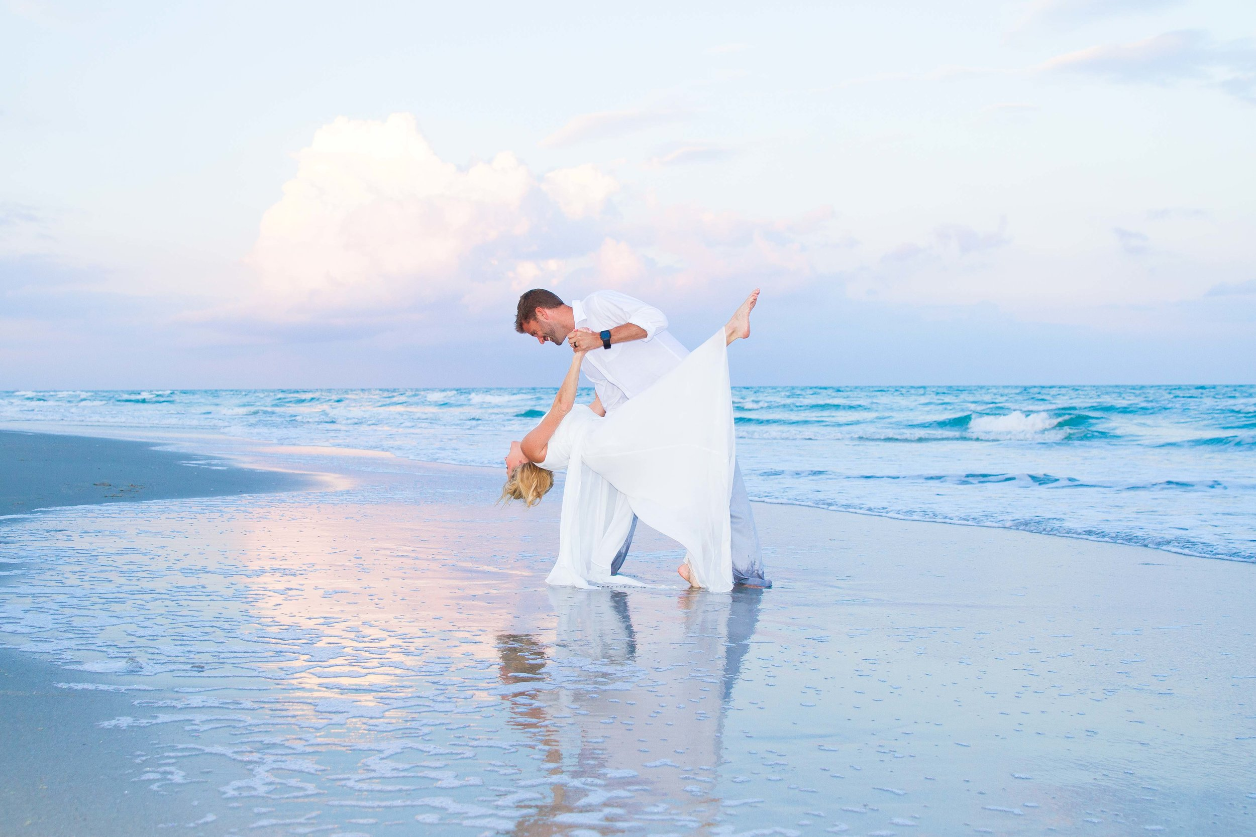 Husband dips his new wife while dancing on the blue beach