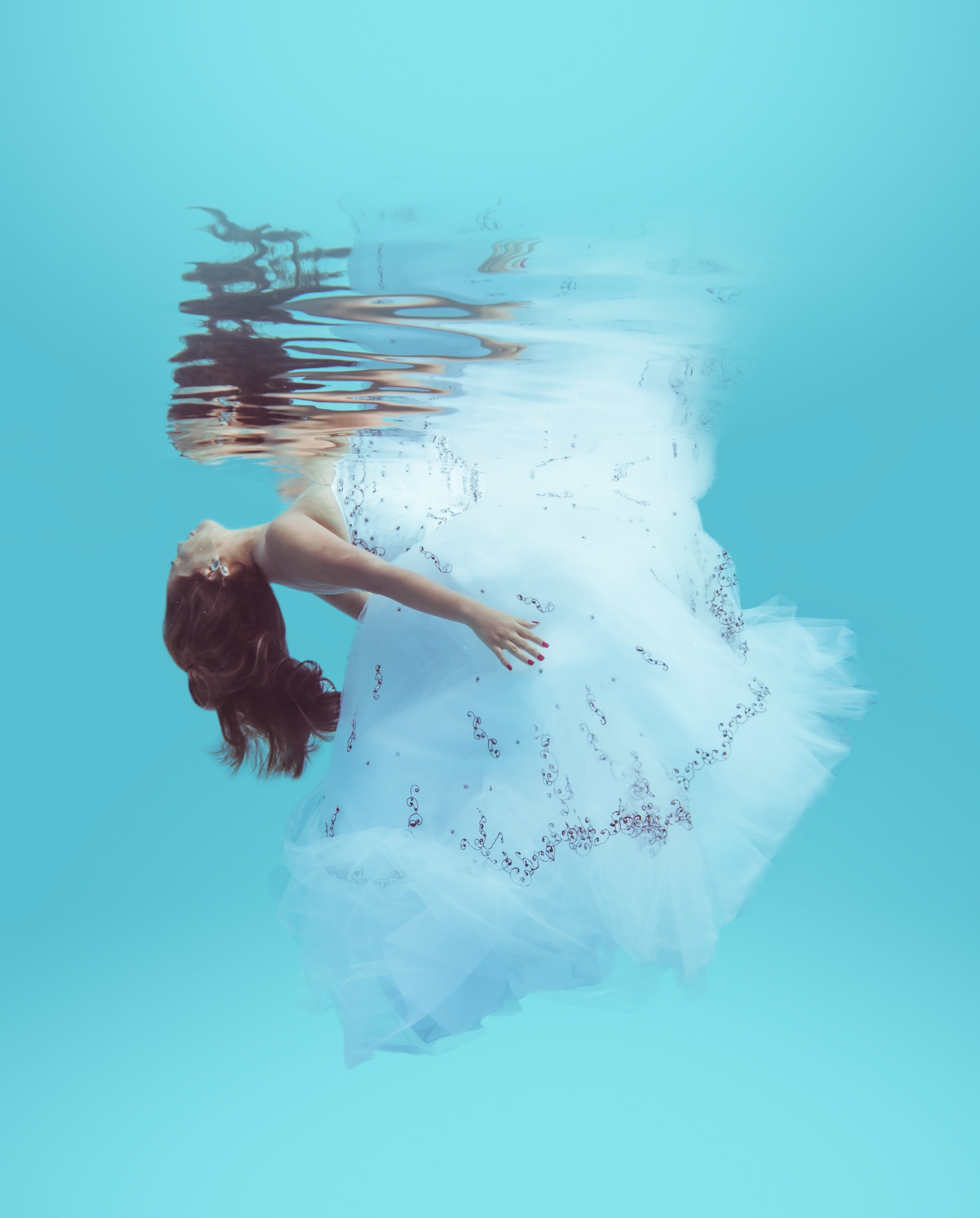 Bride floats elegantly under the water in her wedding dress