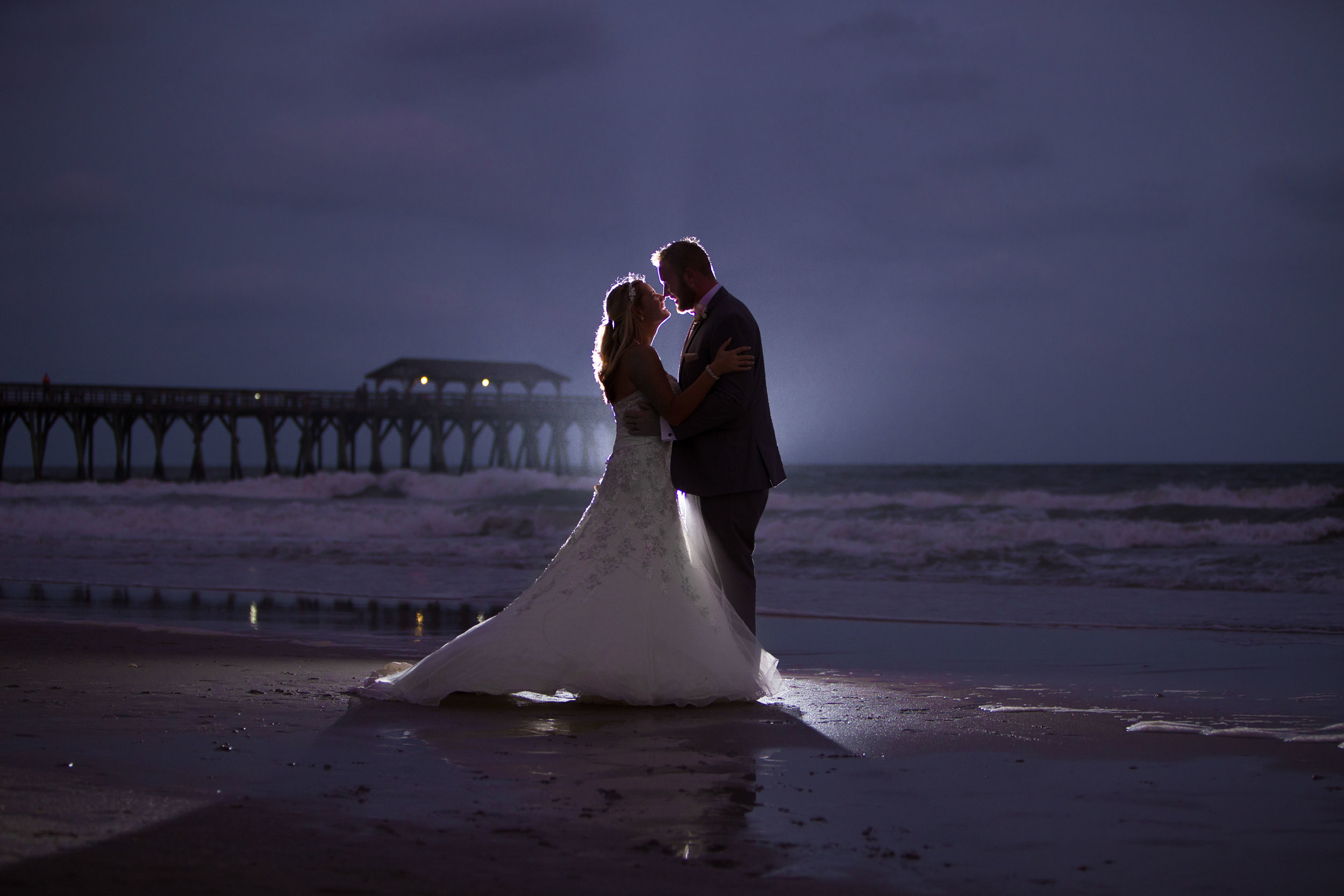 Wedding pictures of Couple kissing at  night at Myrtle Beach Springmaid Pier with the ocean behind them