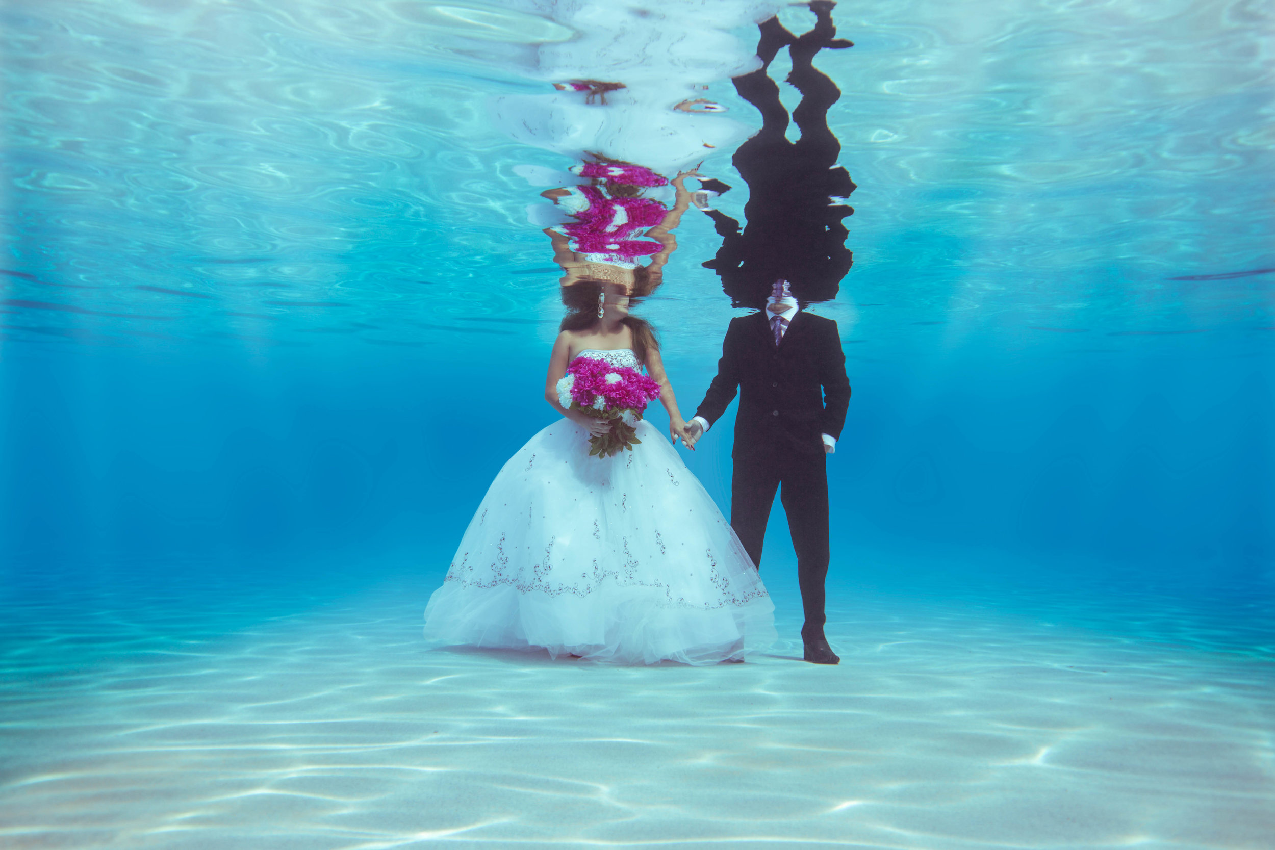 Underwater Photography in Myrtle Beach of bride and groom holding hands and wedding bouquet