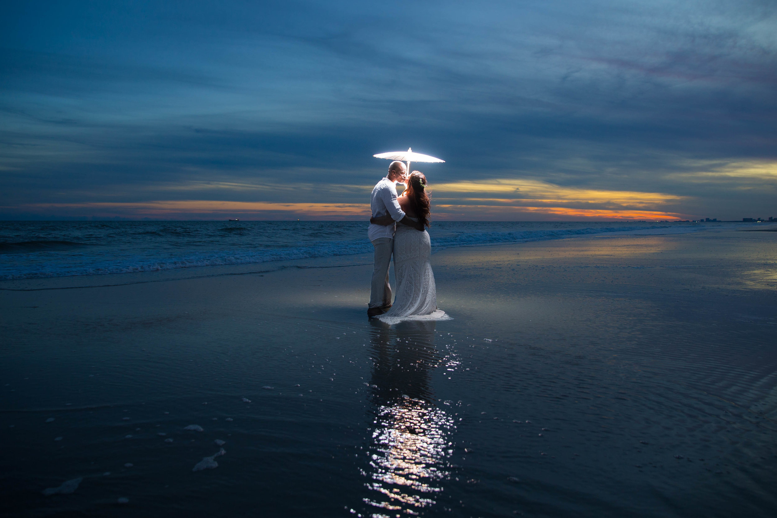 Couple kisses on a beach during sunset with an illuminated umbrella.