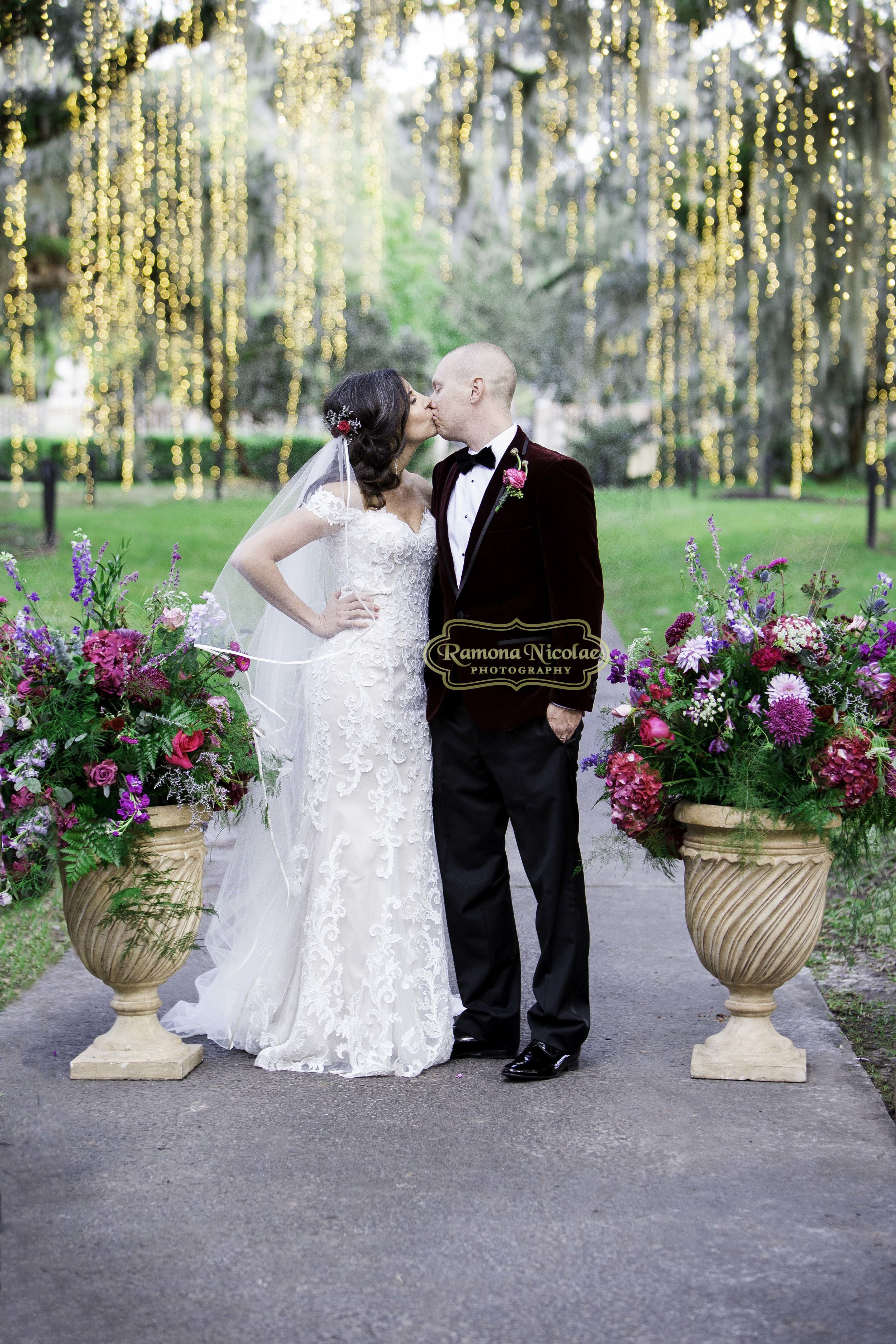 bride and groom kissing at brookgreen gardens during night of thousand lights after their wedding.jpg