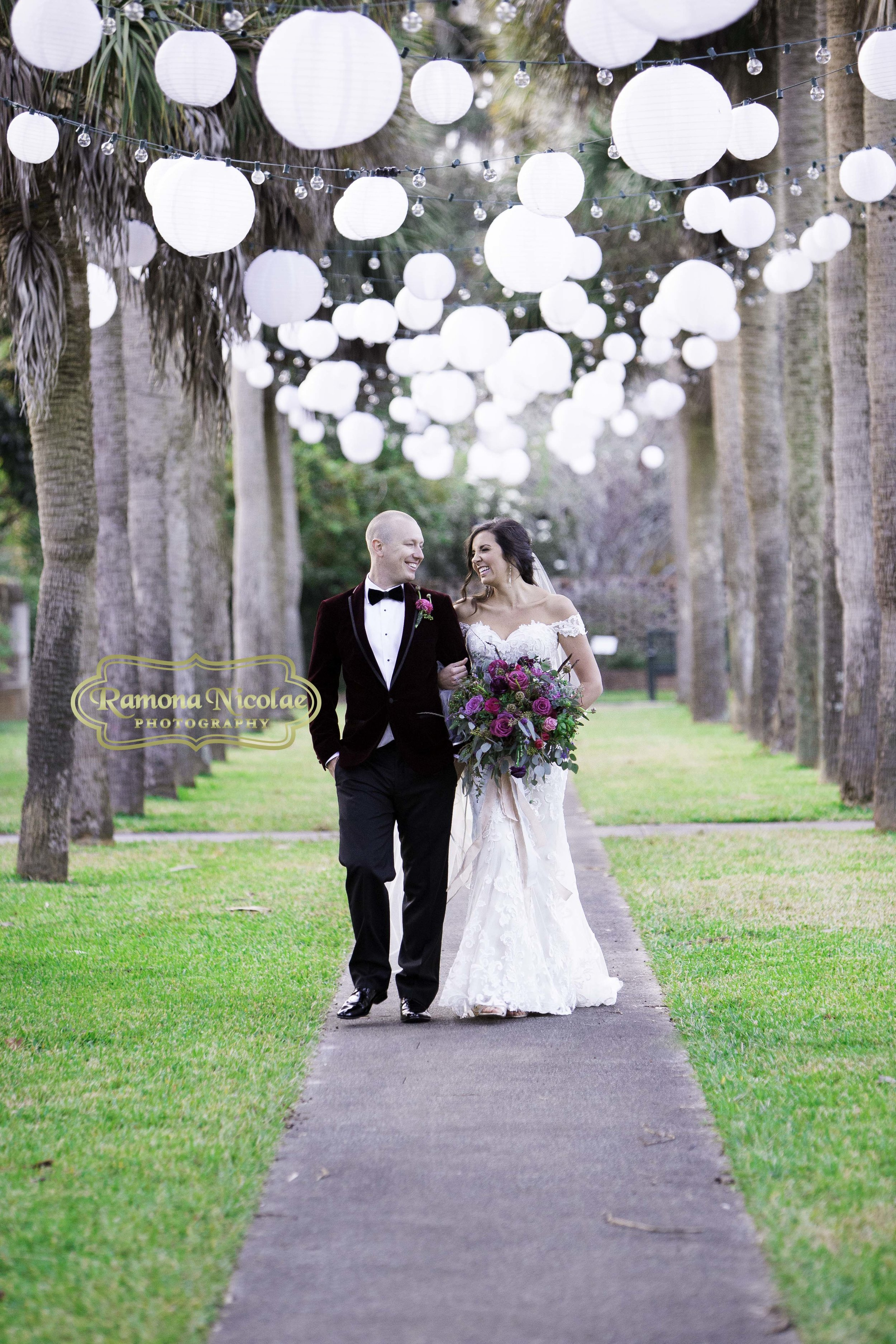 bride and groom walking at brookgreen gardens on their wedding day laughing holding wedding bouquet.jpg