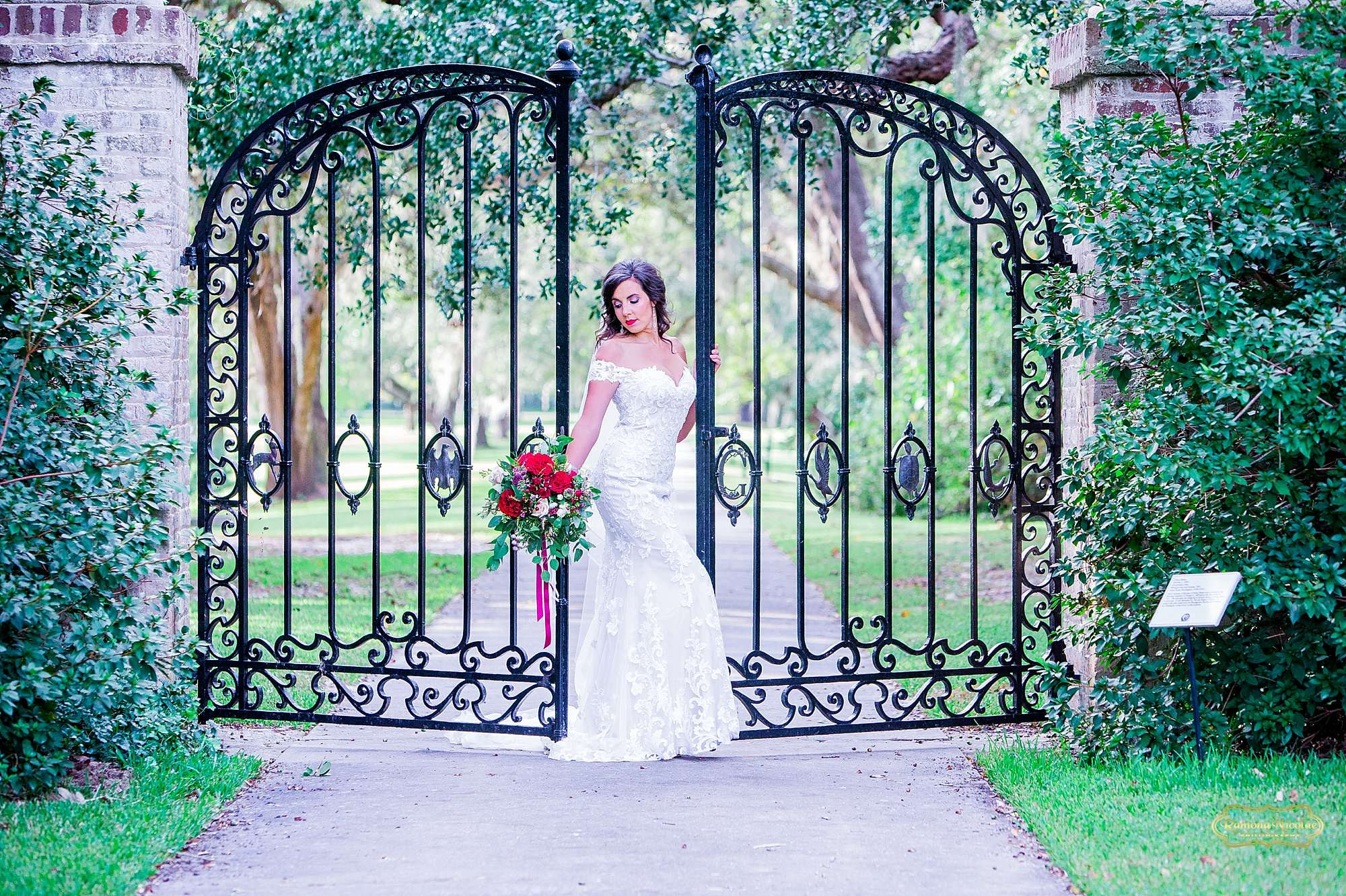 bride with red flowers by the black B & G gates at Brookgreen Gardens looking gorgeous during bridal session with ramona nicolae photography-12.jpg