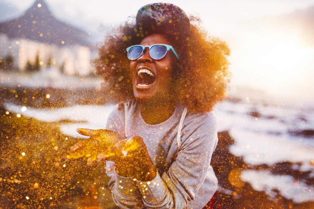 afro-hipster-girl-laughing-ecstatically-while-throwing-gold-glitter-picture-id469247014.jpg