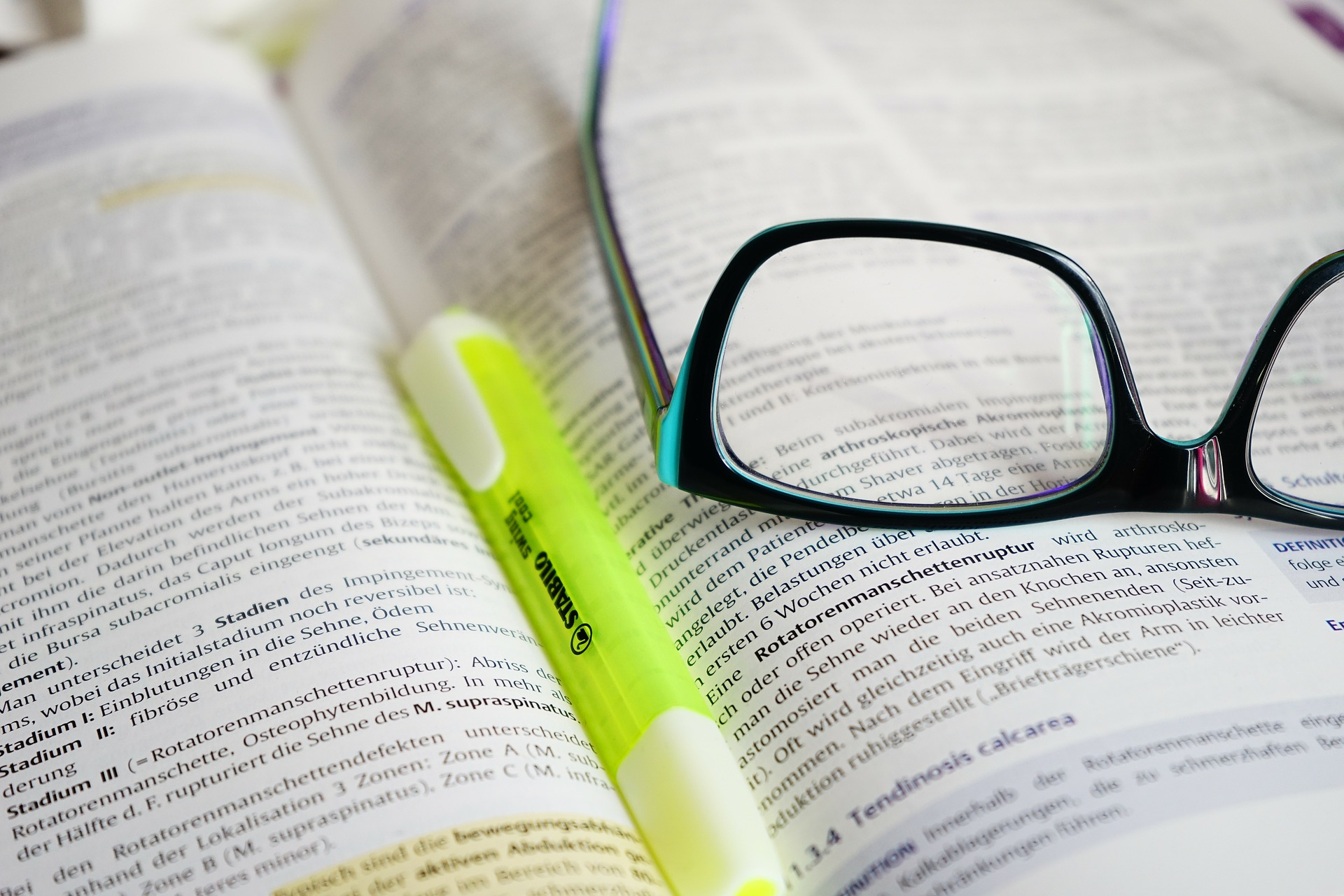 Textbook with glasses and highlighter