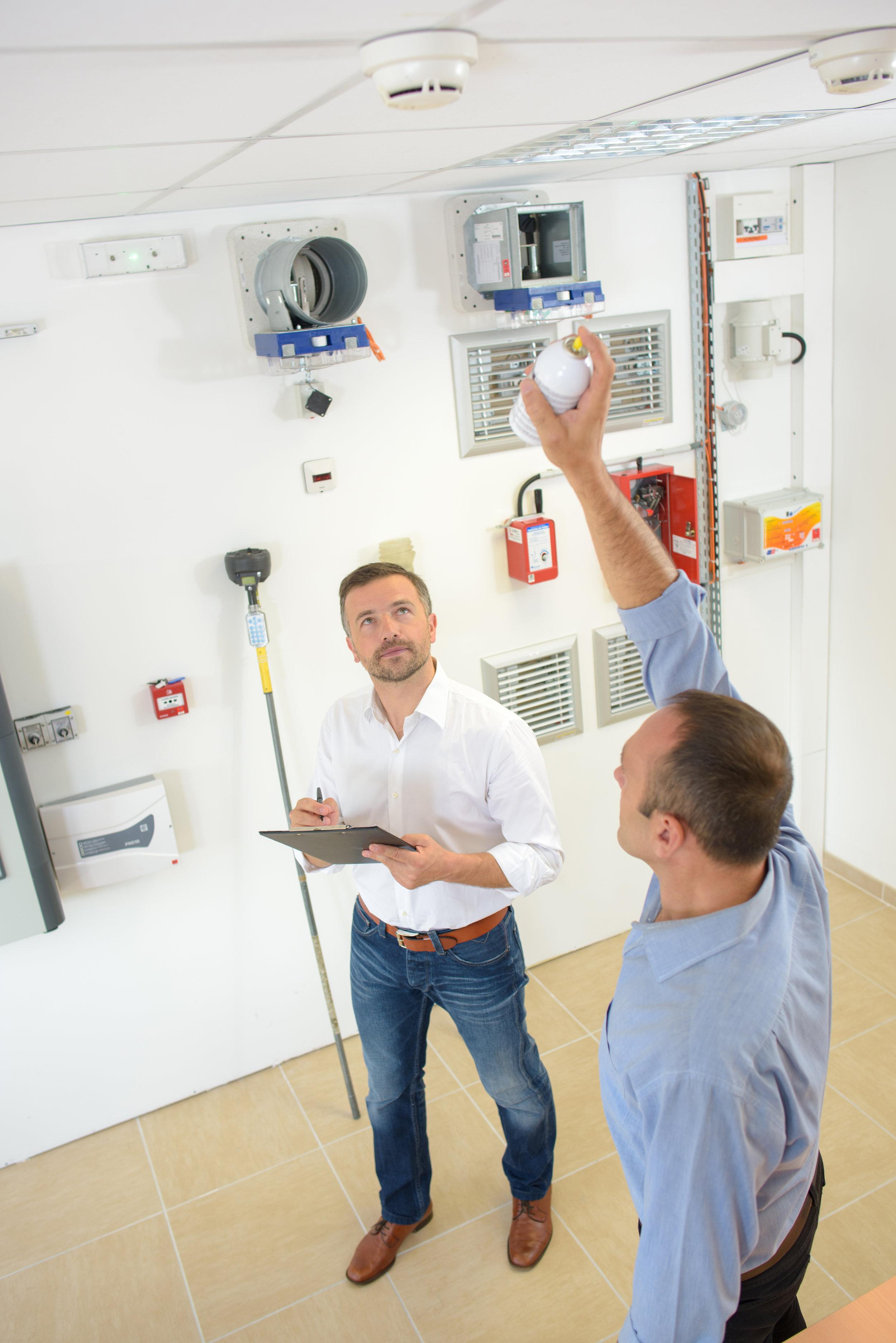 fire alarm inspector checking an alarm