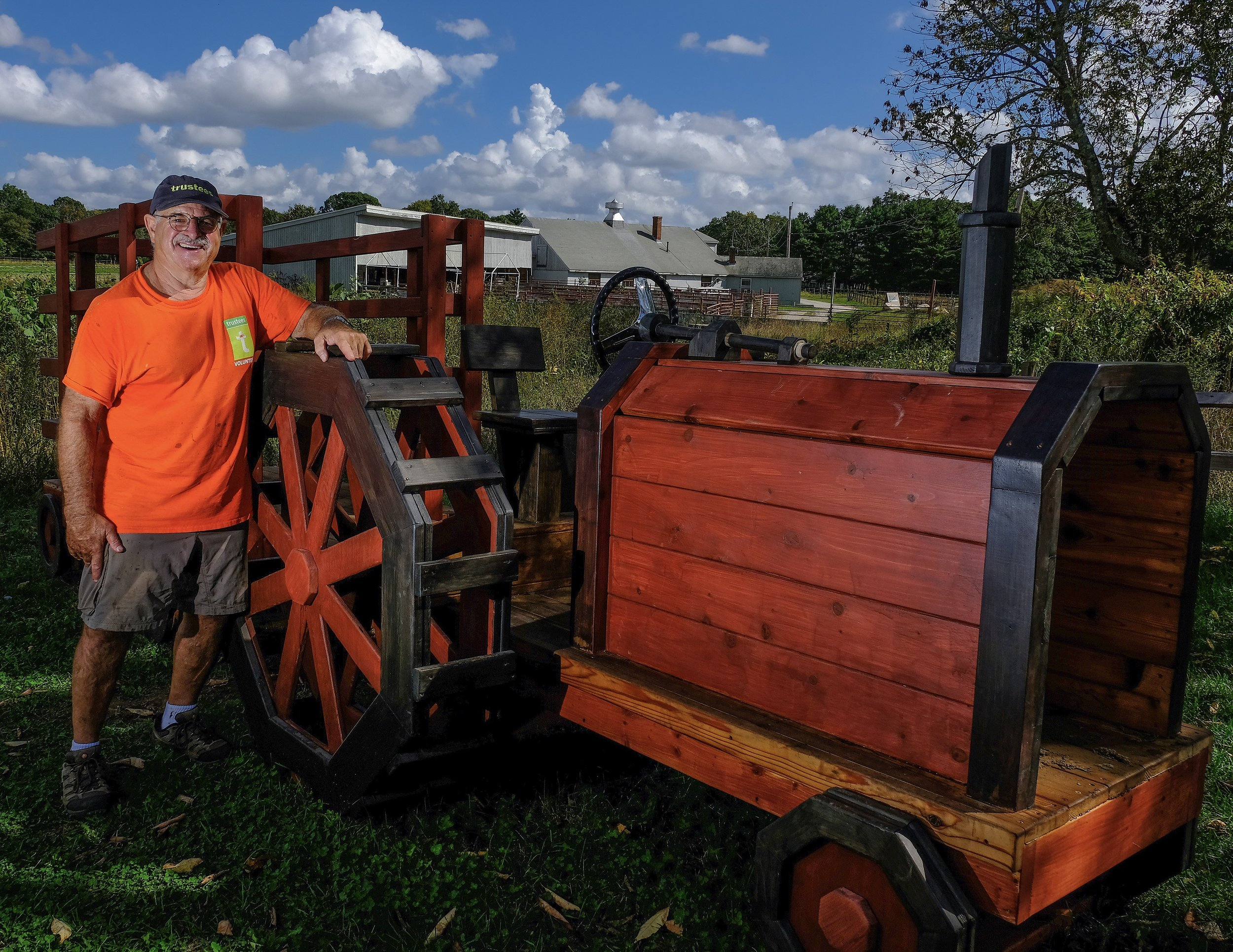 Alan Pasnick stands proudly next to one of his most recent creations, a tractor pull built for the kids play area at Powisset Farm in Dover.