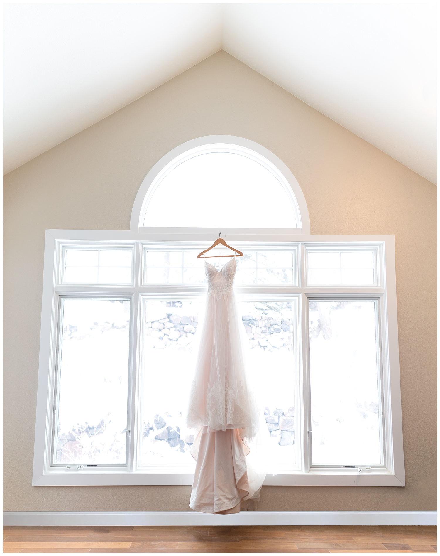 Wedding dress hanging in a brightly lit window
