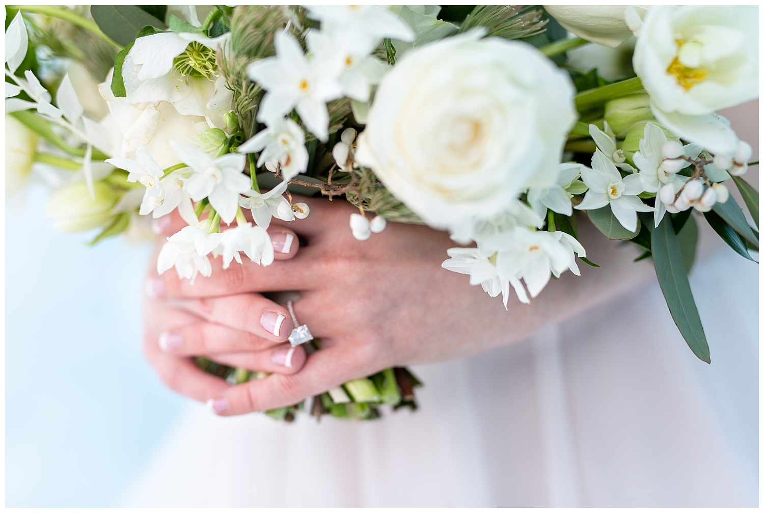 close up photo of a ring on the bride's hand while holding her bouquet