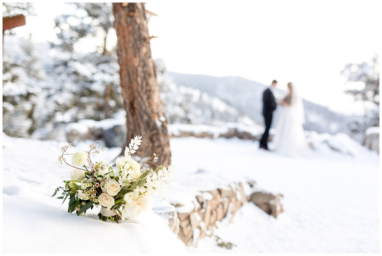 a bouquet sits in the snow with a bride and groom showing in the background
