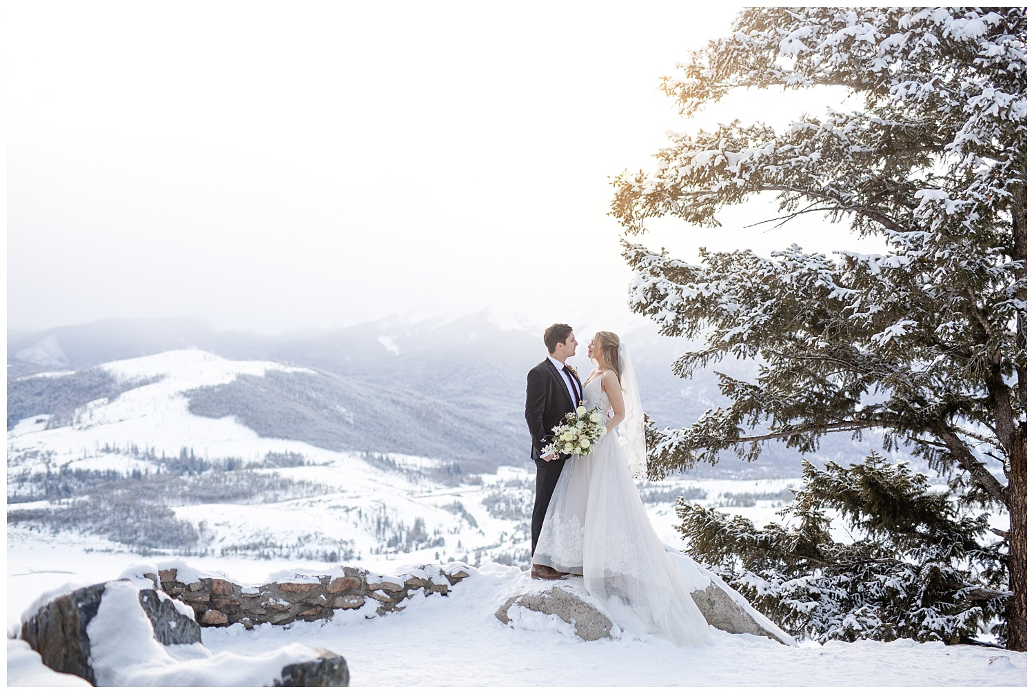 A bride and groom stand on the side of a mountain at Sapphire Point Overlook in winter