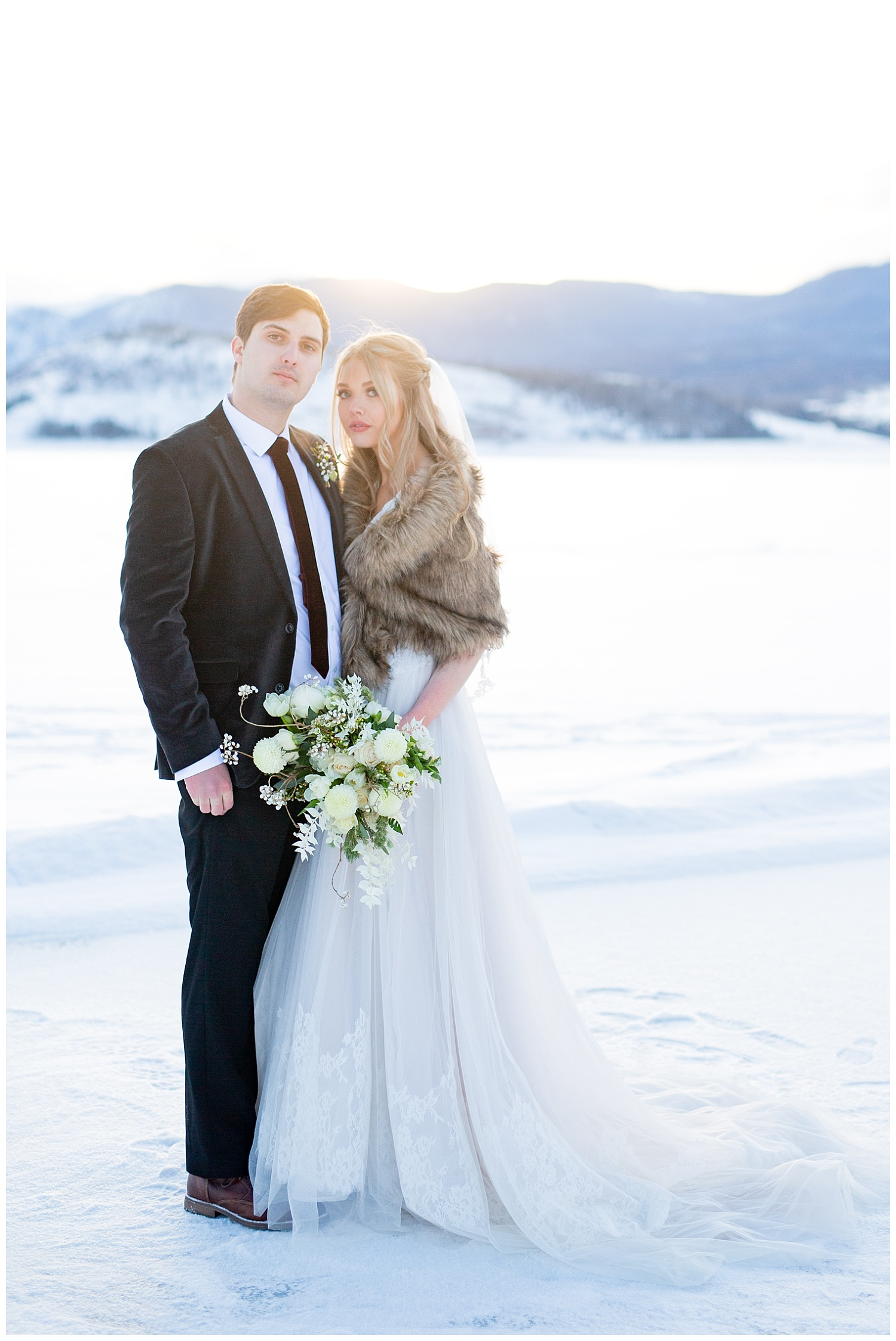 A bride and groom on a snowy lake in the middle of winter