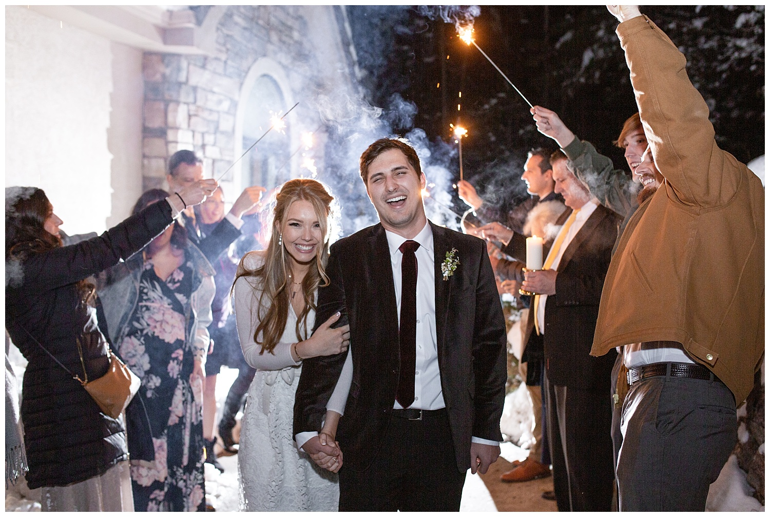 The groom laughs as the smoke from their sparkler exit lights up behind them