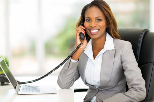 Image description: Business person holding a phone conversation at their office desk while smiling.