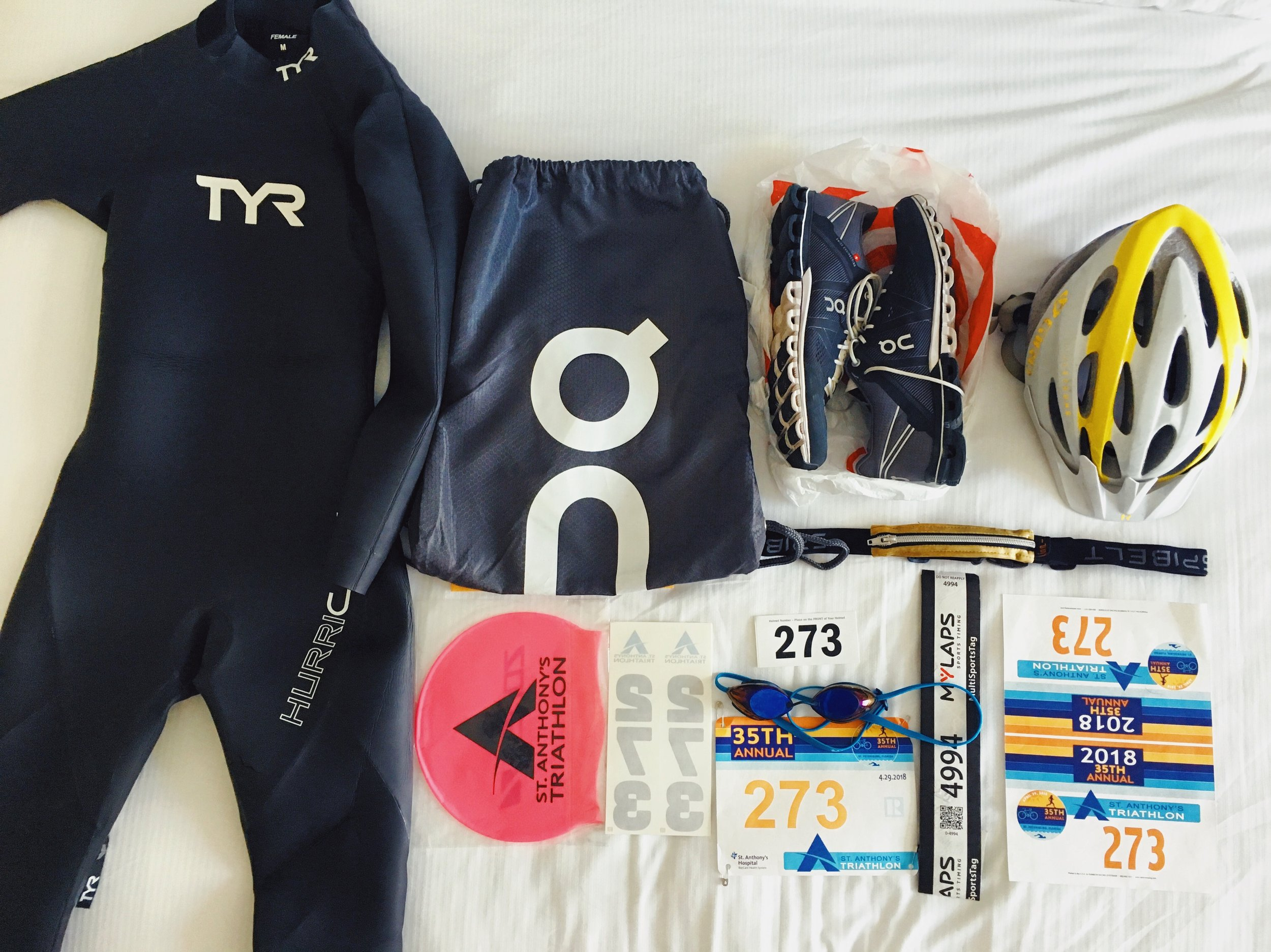 TYR Hurricane Wetsuit  , On Running backpack ,     On Running Cloud Flows ,  Spibelt Gold Race Belt ,  Giro Xara Helmet    ,  Speedo Vanquisher Goggles