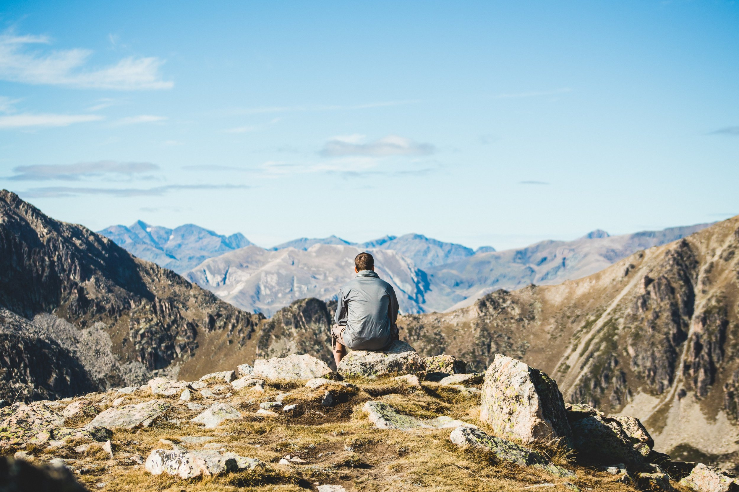 Man sitting on rock looking at mountain scenery.