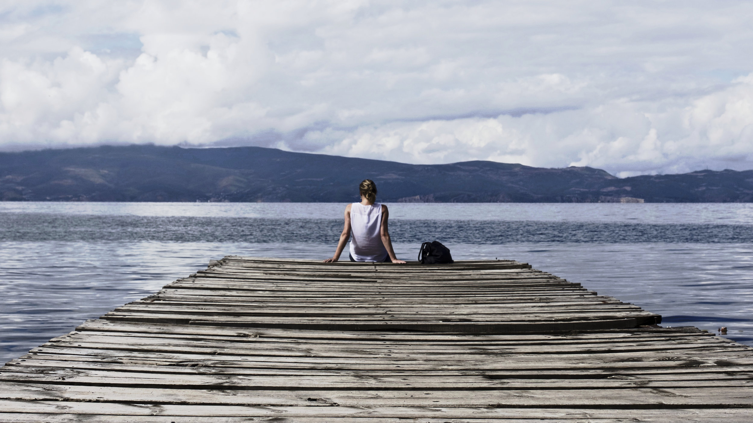 Woman sitting on dock looking out at mountains and lake.