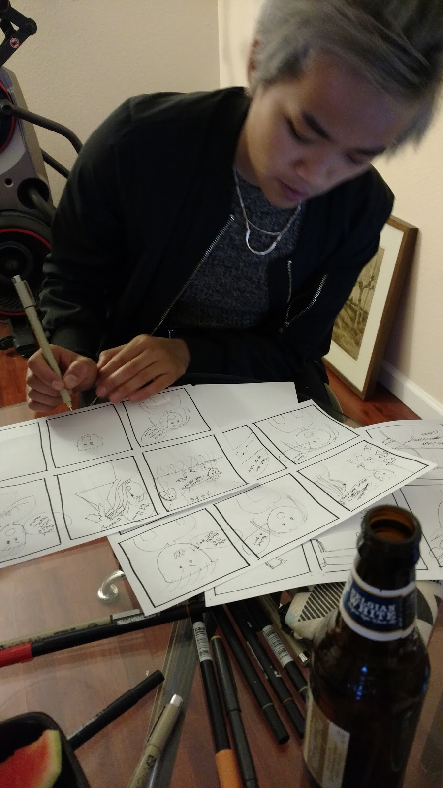 Director Sal Tran sketches images on stacks of storyboard grids. There are pens and markers across the table