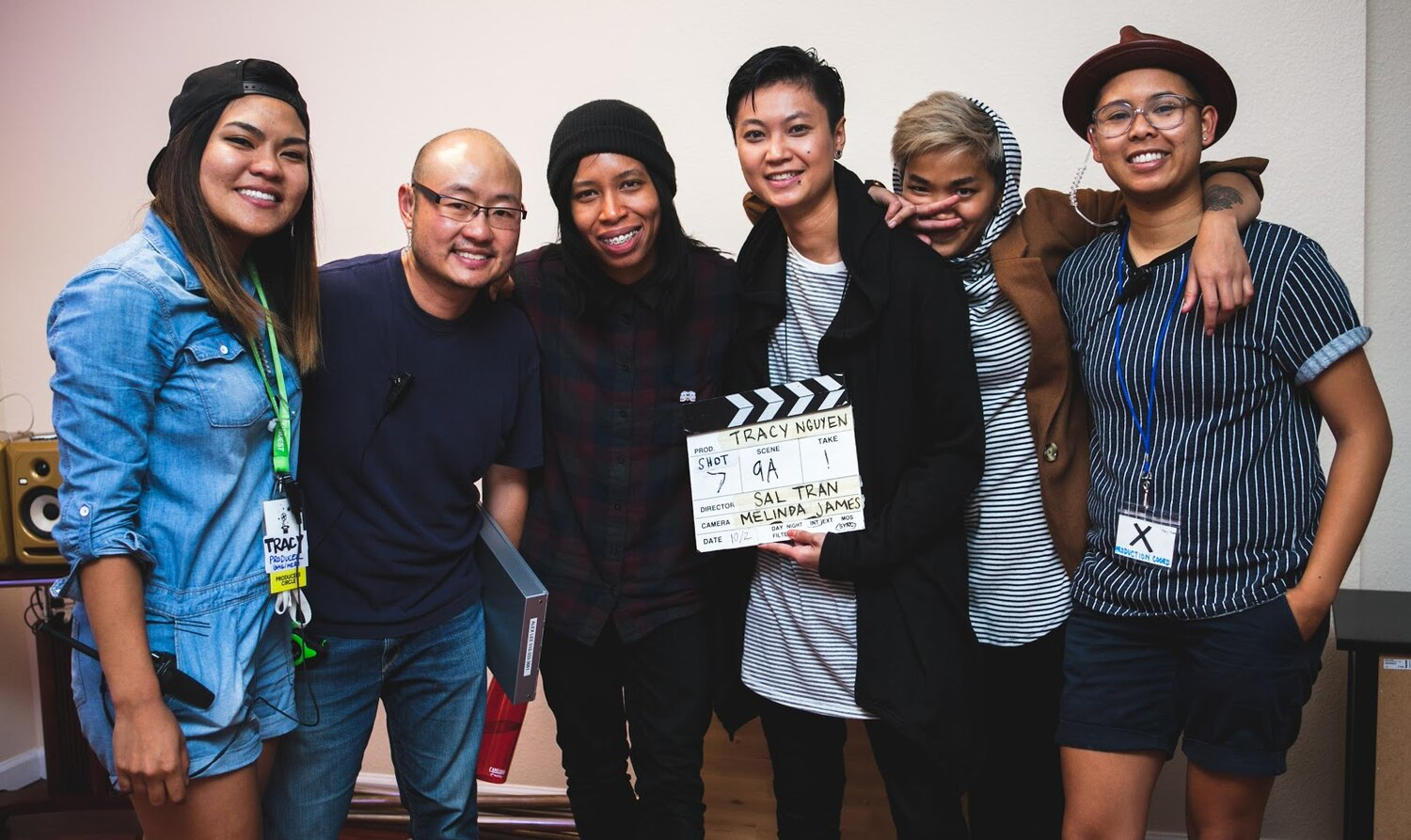 Six people smile with their arms wrapped around one another. At the center is a film slate. Alex Lee is pictured second from the left]