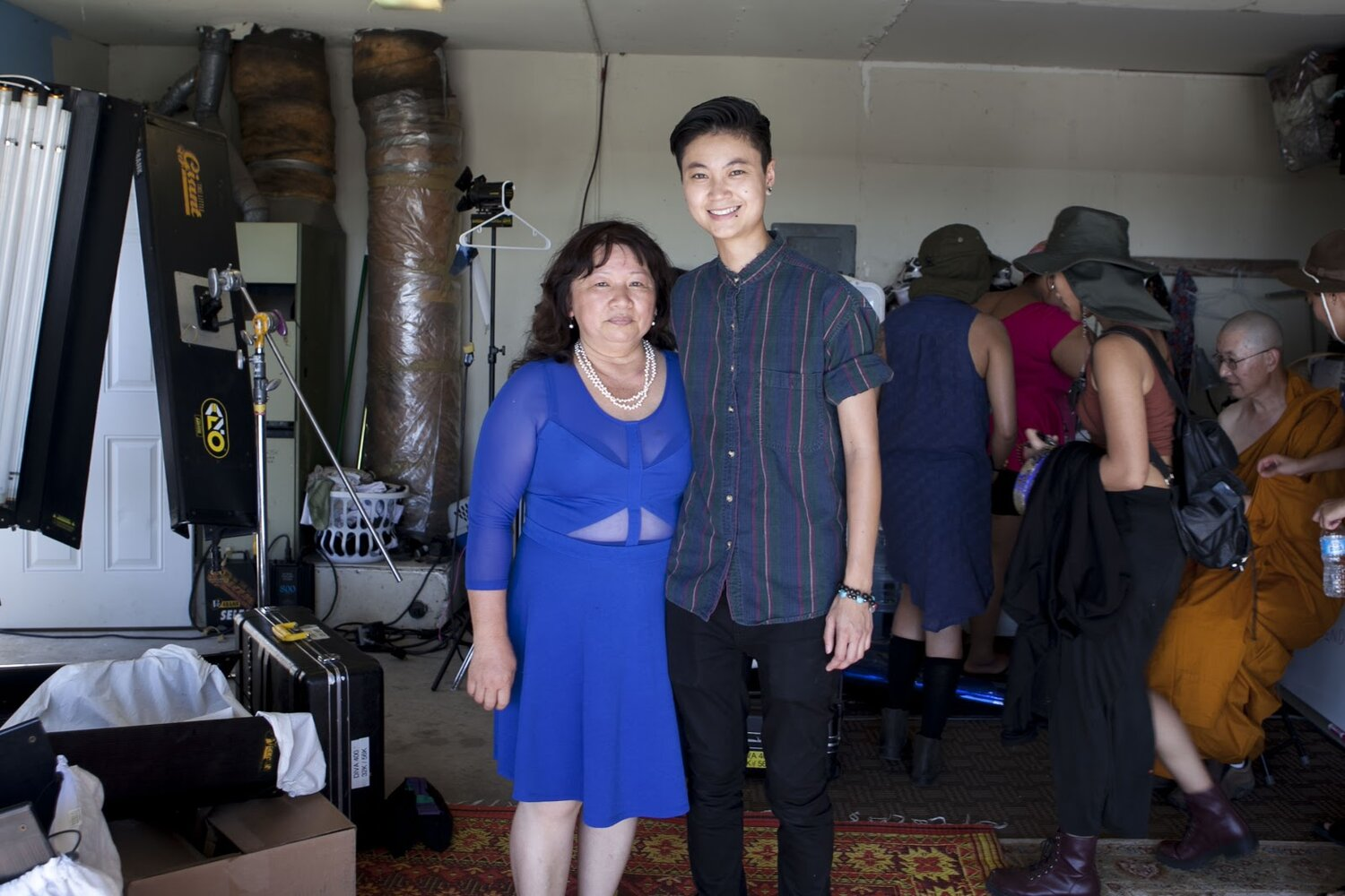 Actress Thu Pham poses next to Actor Ck Ong in the middle of a garage set.