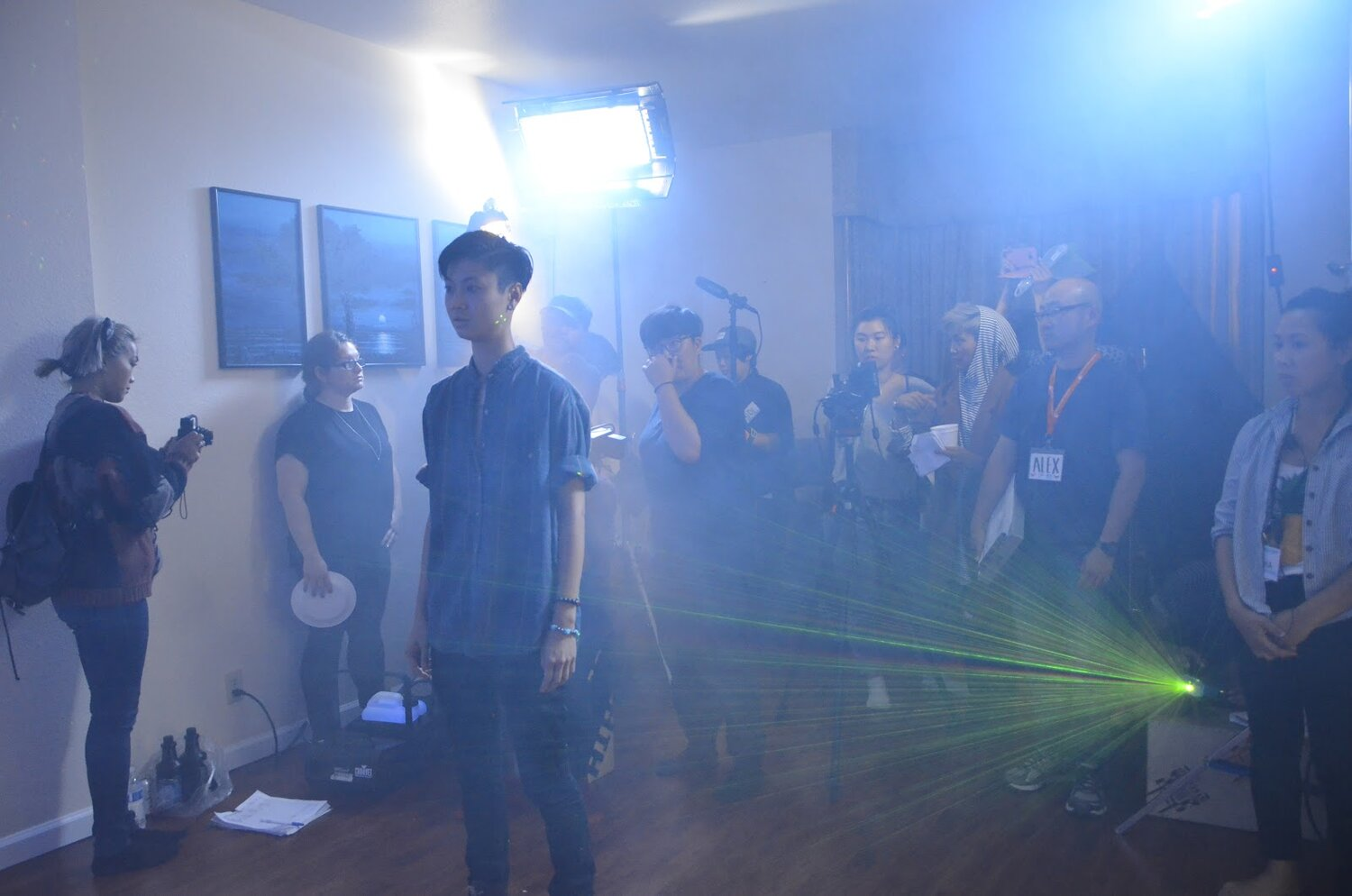 Actor Ck is standing in front of a film crew in a living room filled with fog and green lights.