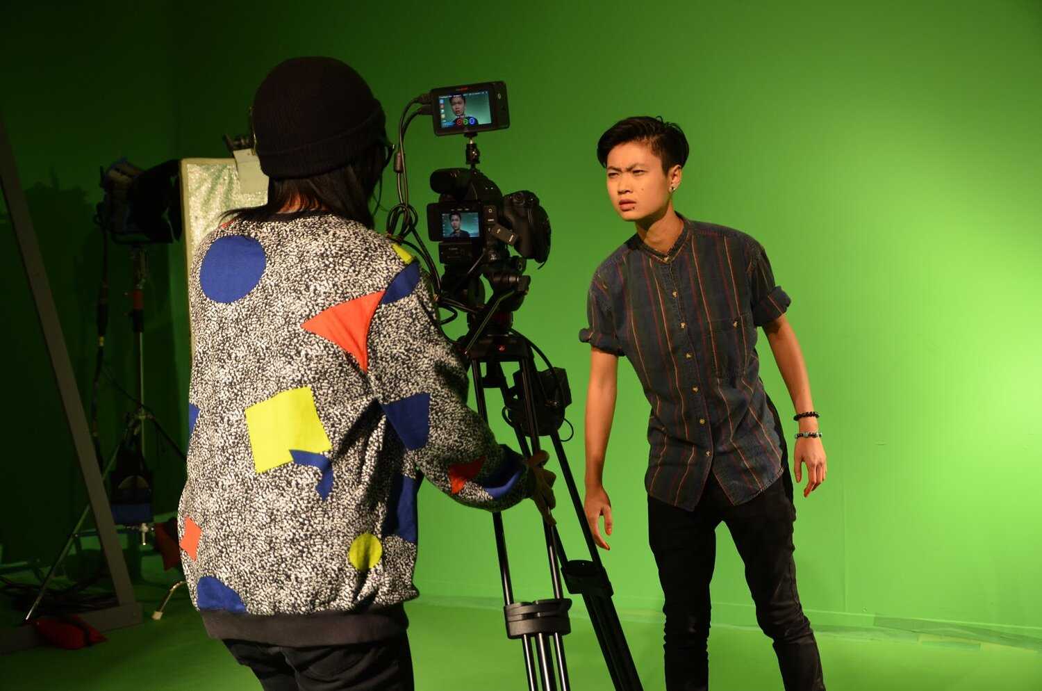 Actor Ck is standing in front of a green screen, looking into a camera, which is operated by Melinda James.