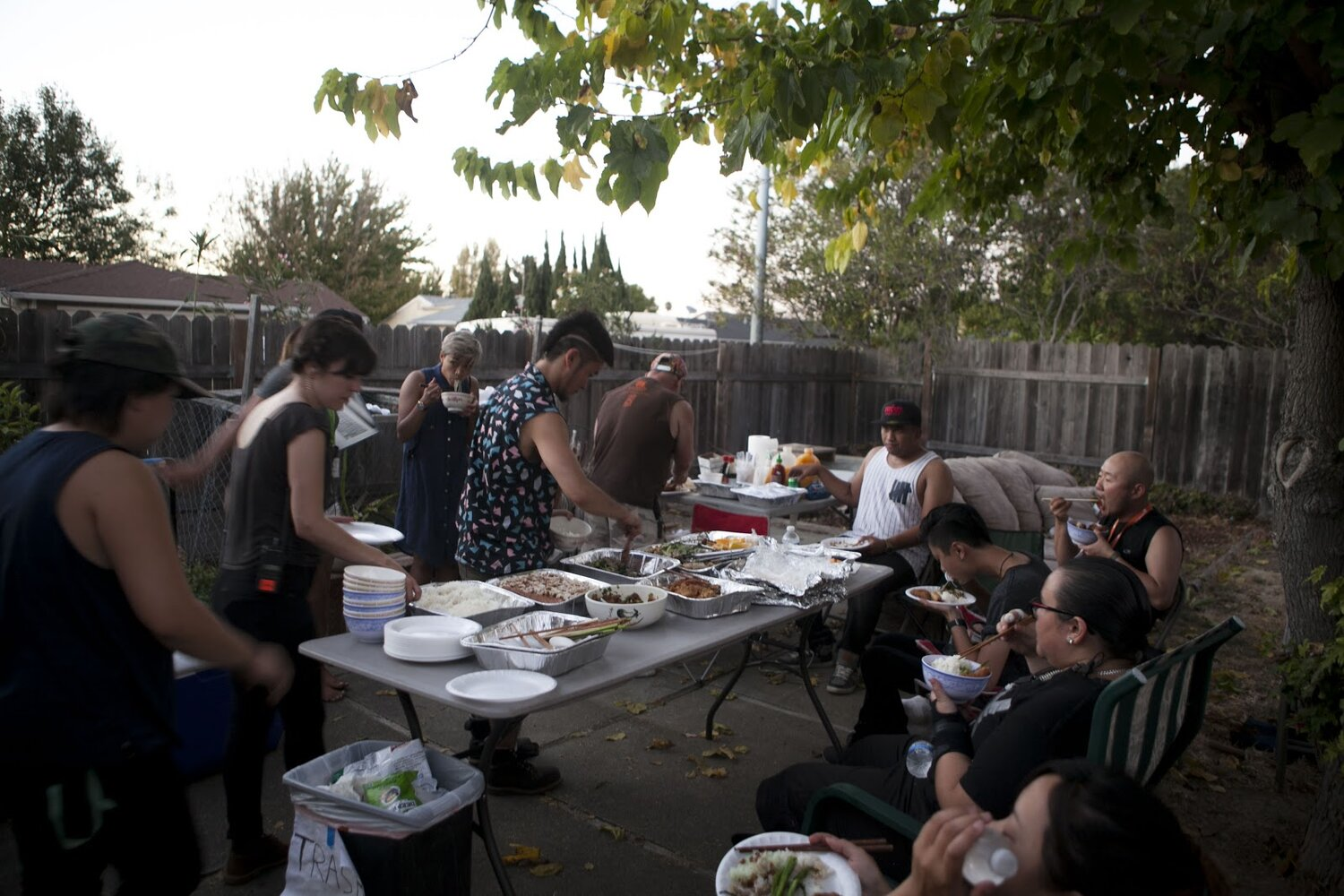 A crew of people are eating in a large backyard.