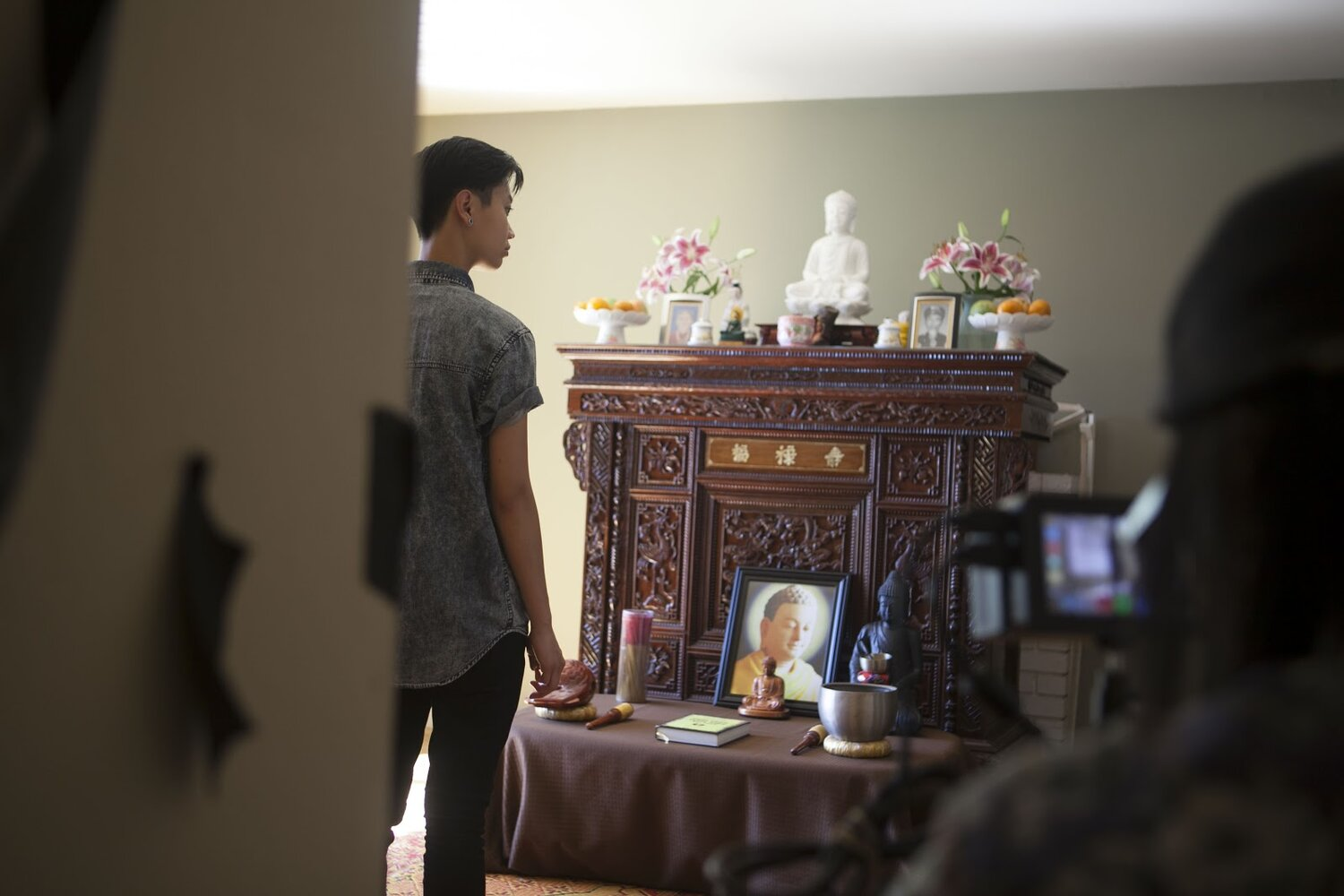 Actor Ck Ong stands in front of an altar adorned with Buddhist photos, statues, incense, and bells.