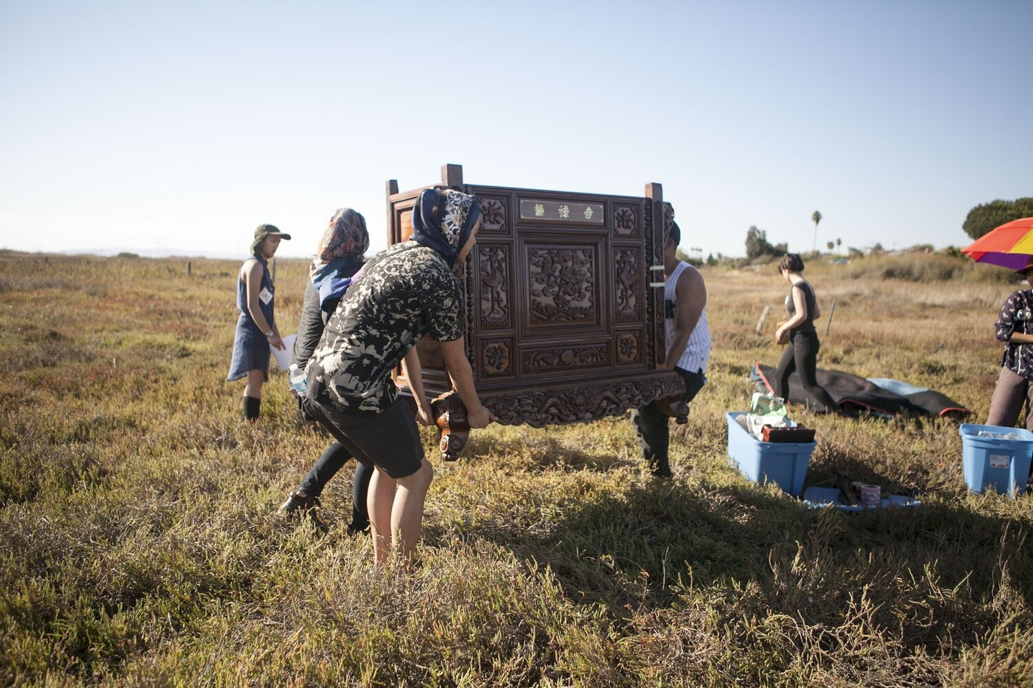 A crew of three people are hauling a 150-lb altar over an open area of dry, grass fields.