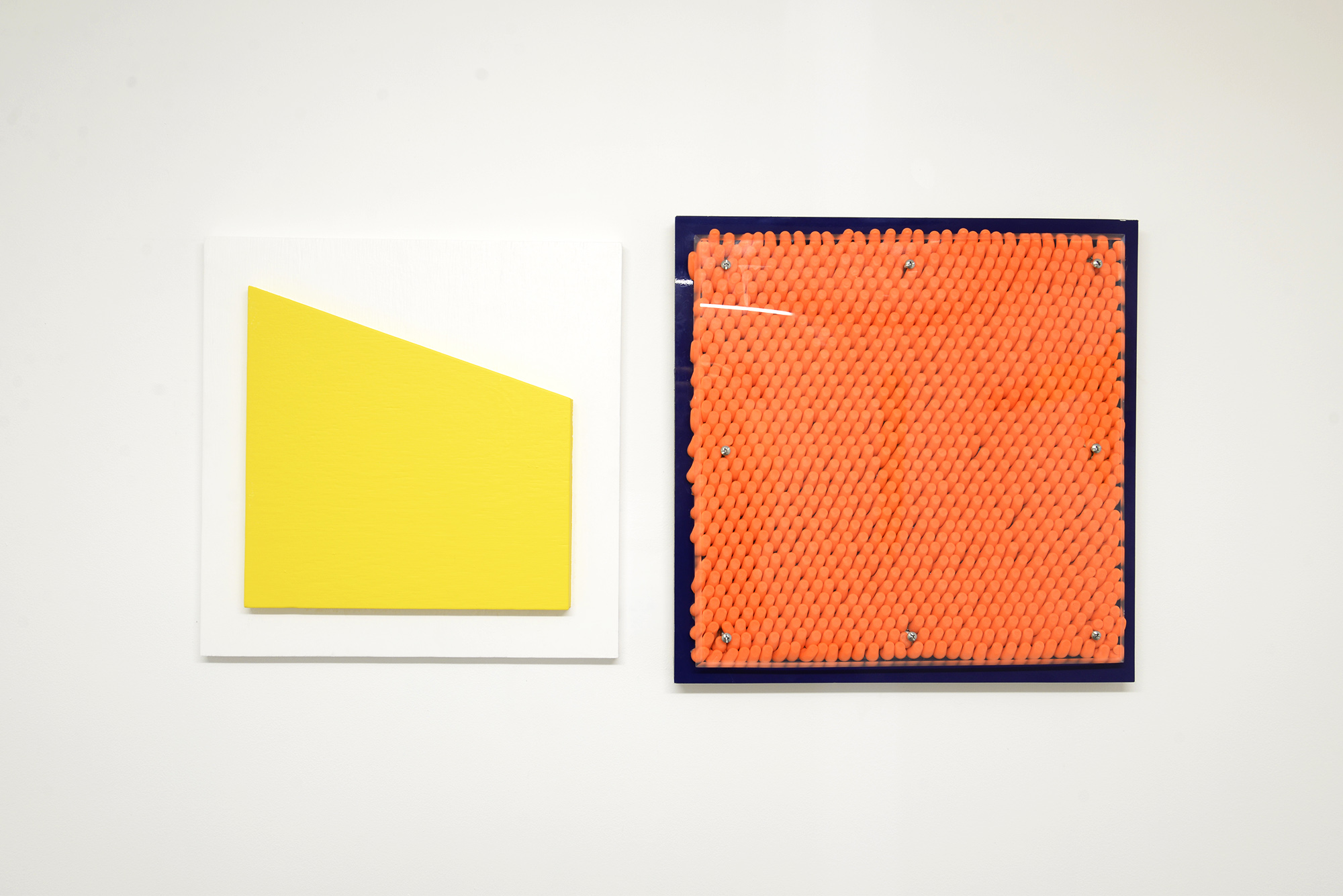 Left: Liam Marsden  100-67  2018 plywood and Dulux Softsun and Vivid White interior paint 30cm x 30cm Right: Jordan Azcune  Hang up , 2018 double plywood, composite aluminium panel, glue, ear plugs, acrylic, screws, washers 50cm x 50cm