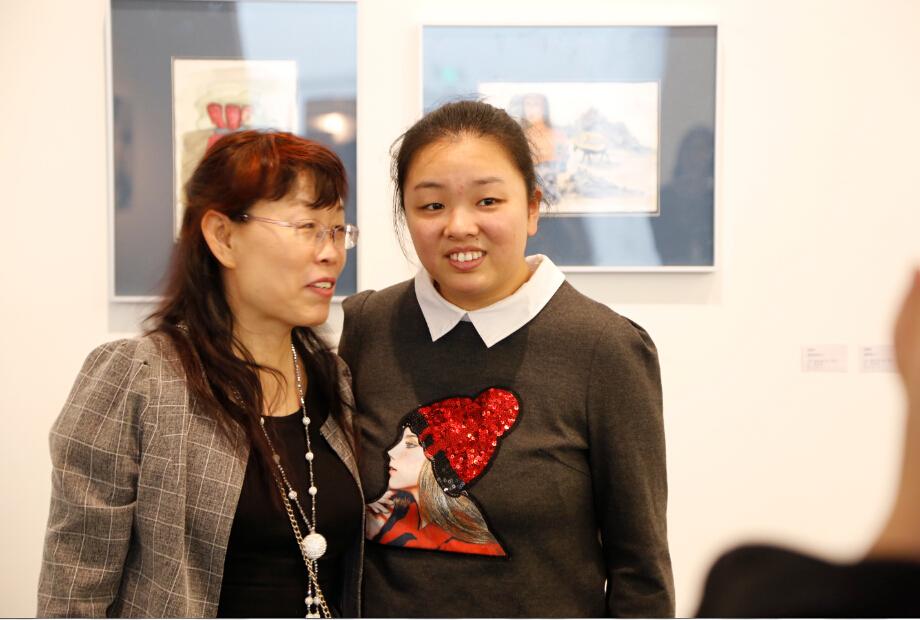 天真者朱婉君和母亲在艺术家张晓刚画作前.jpg