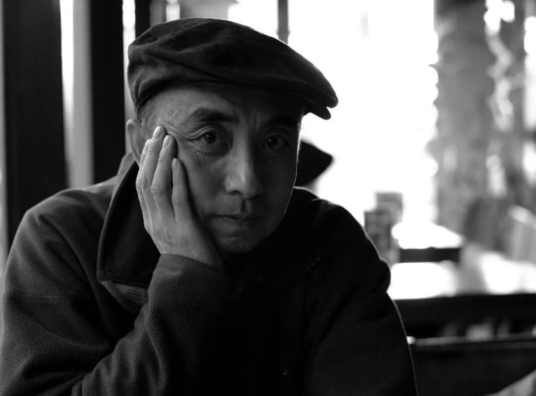 """张晖   1968年生于北京,父母分别从事民乐演奏与舞蹈。1987年,张晖进入中央美术学院壁画系学习,此时壁画系刚刚成立四年,这个新科系对于新绘画材料和观 念抱有非常包容的心态,使他可以自由的进行绘画实验。1991年毕业后,他一直利用业余时间从事绘画, 1995年成为职业画家。2000年,张晖赴美,后来进入明尼阿波利斯艺术学院学习新媒体艺术,在学习期间他更多专注于与专业学习有关的新媒介的相关探索。然而新媒体的创作在研究生毕业后就停止了,他选择回归到熟悉的绘画领域。2007年,他重新回到北京。这座城市的面貌已经发生很大变化,他的绘画开始频频记录这座城市的日常景象,用高饱和的、明亮的颜色描绘出城市日常生活的诗意。作品《风景2016之一》《柿子树2018.1》《花之一》参展中间美术馆""""快乐的人们……""""展。"""