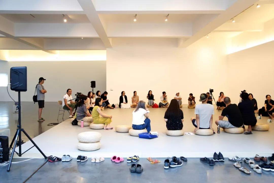 活动现场,观众与对谈嘉宾一起围坐在展场中特别搭建的舞台上