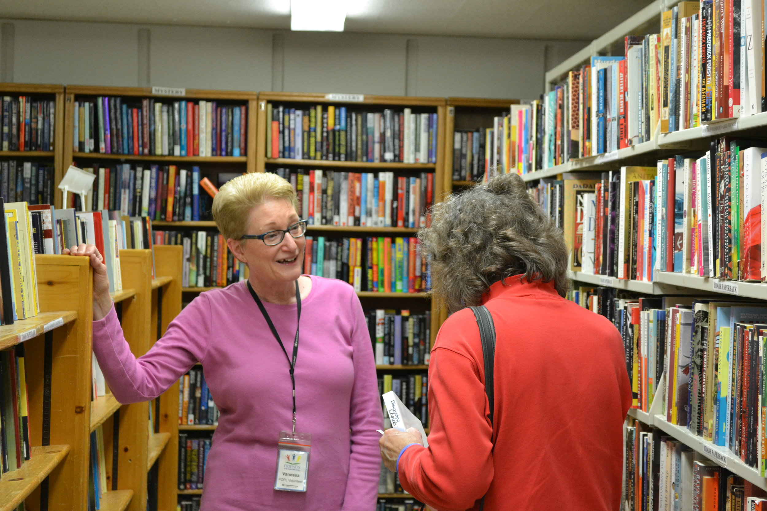 Friends volunteer helping a book sale customer.