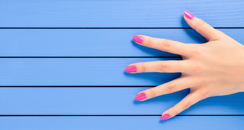 Female-hand-with-pink-nails-on-blue-wooden-background.jpg