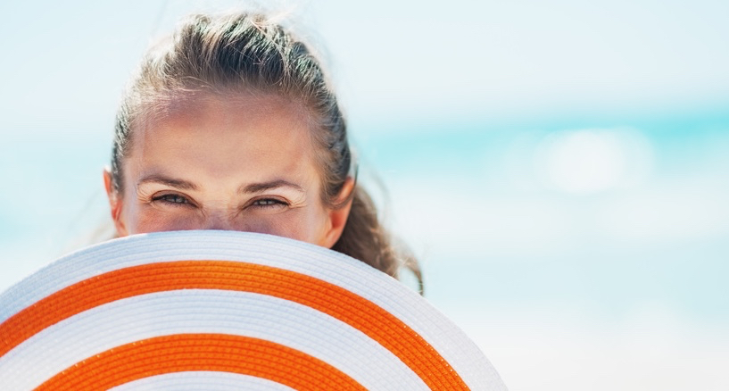 Portrait-of-happy-young-woman-in-swimsuit-hiding-behind-beach-hat.jpg