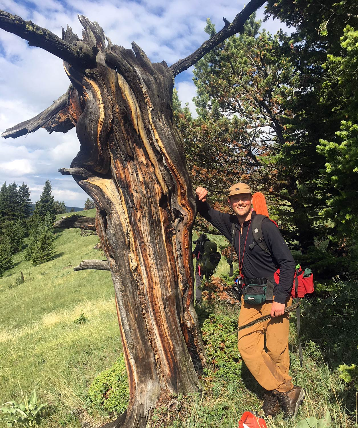 Owen Fitzpatrick of the Landscapes in Motion Fire Regime stands next to a fire-scarred tree in the southern Rockies of Alberta.