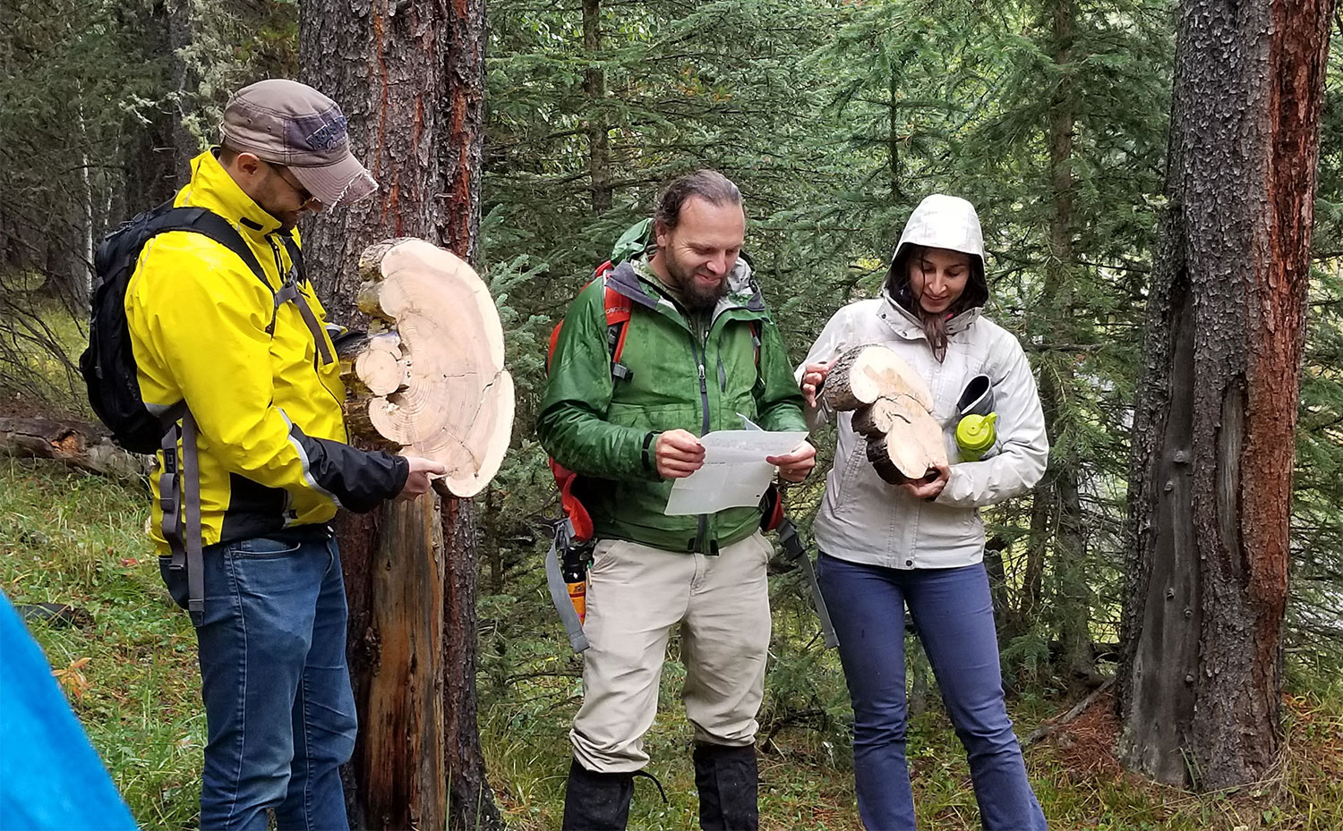 Cameron (centre) is flanked by Alex Chubaty (fRI Research) and Ceres Barros (Landscapes in Motion) as they hold up fire scarred tree cookies. Photo by S. Odsen.